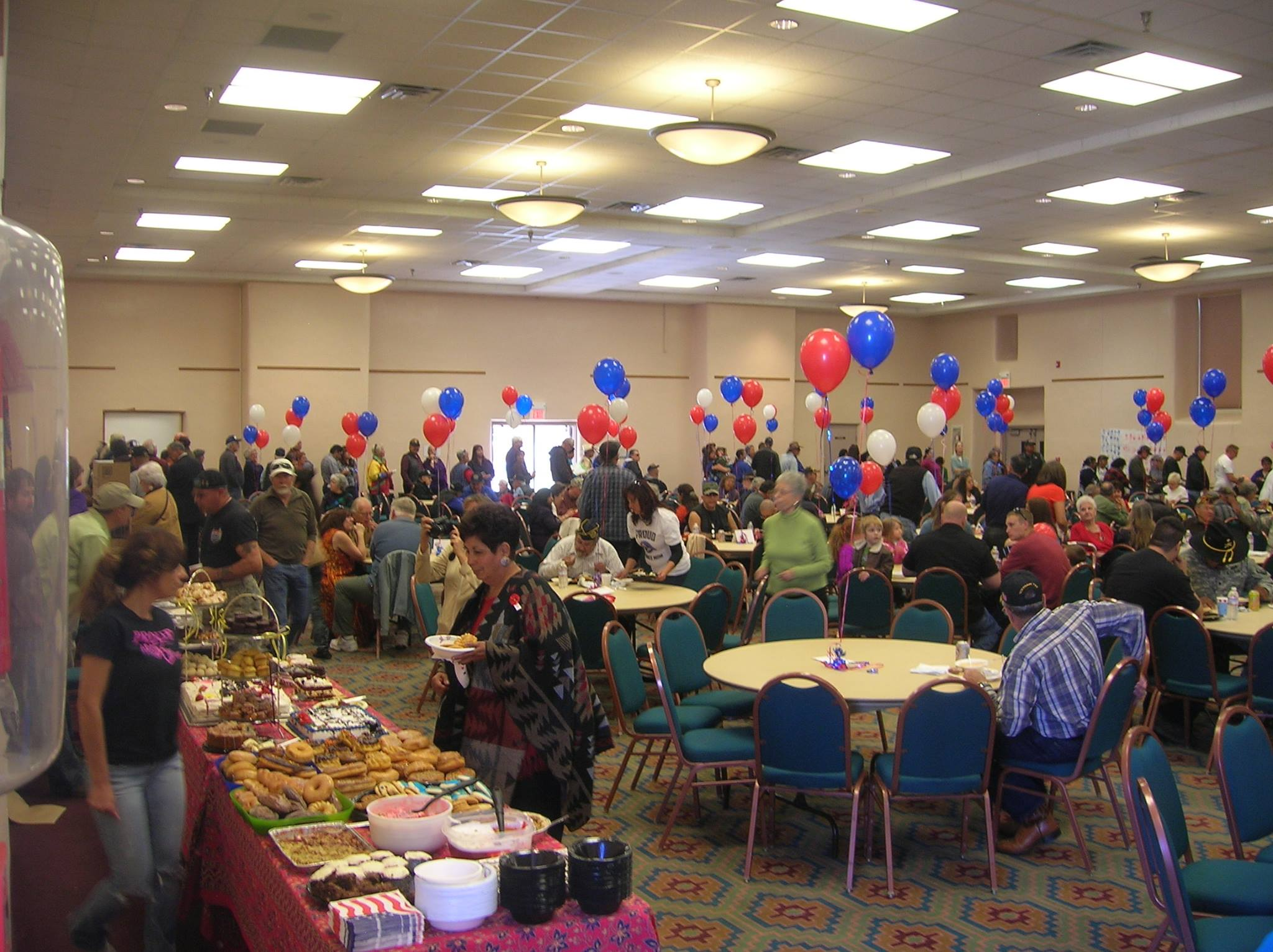 Big crowd in bright event room, cornucopia of baked goods in foreground, red, white, and blue balloons floating throughout