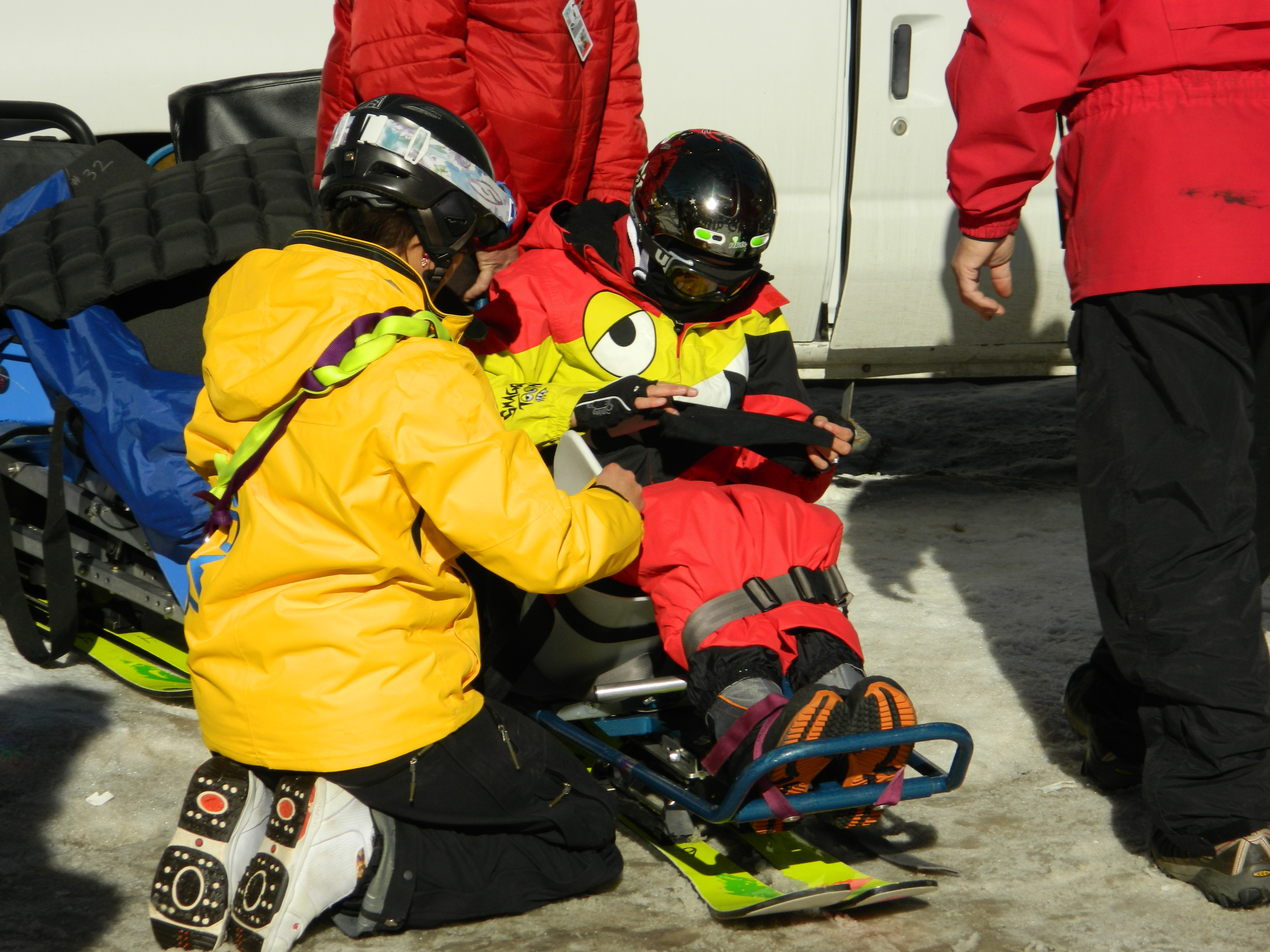 A Taos Ski Valley instructor kneels to assist a disabled skier in a ski chair in the parking lot. Two other skiers help.