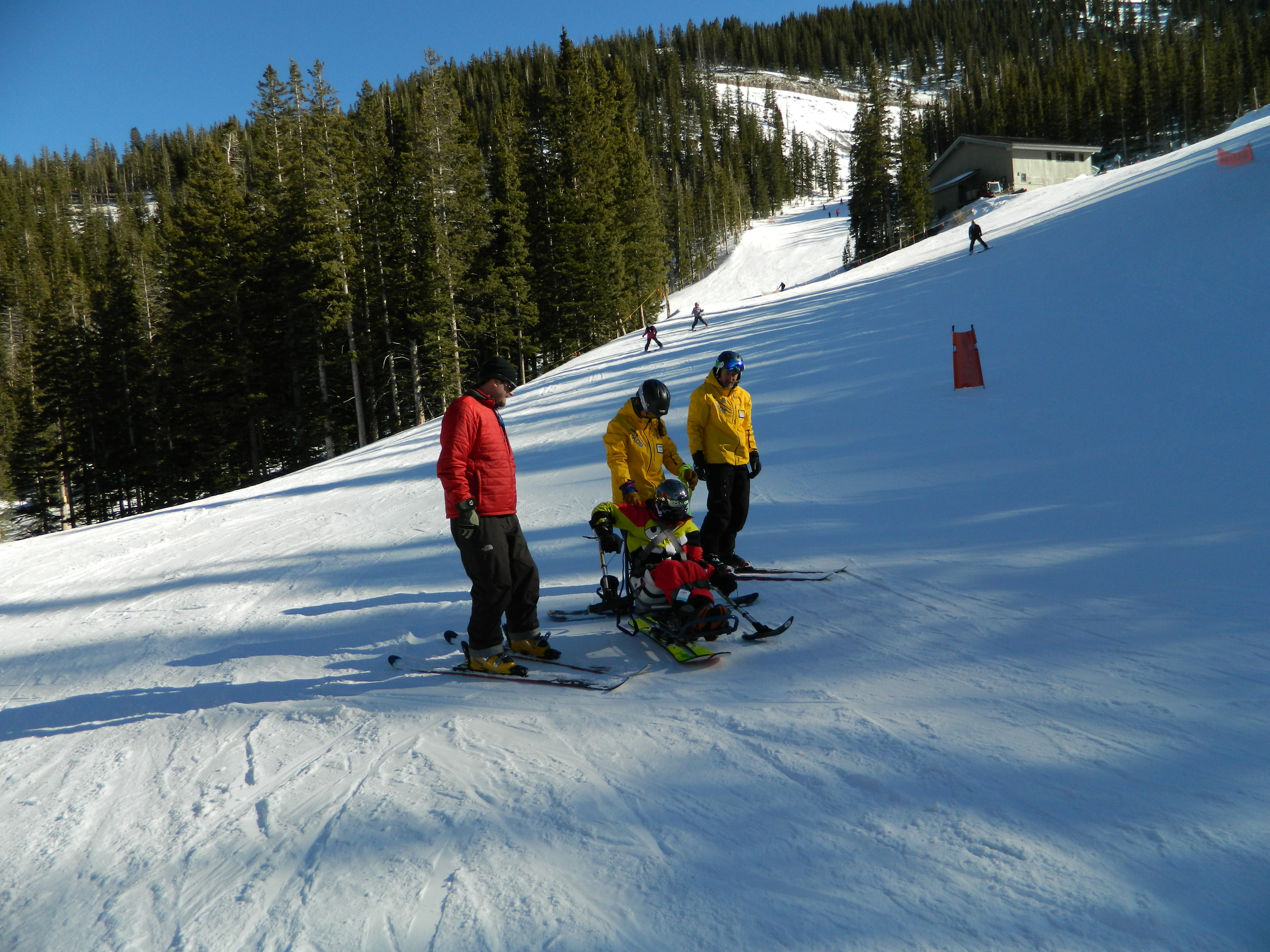 Two Taos Ski Valley instructors in yellow coats and a third skier assist a disabled skier in a ski chair on the slopes.
