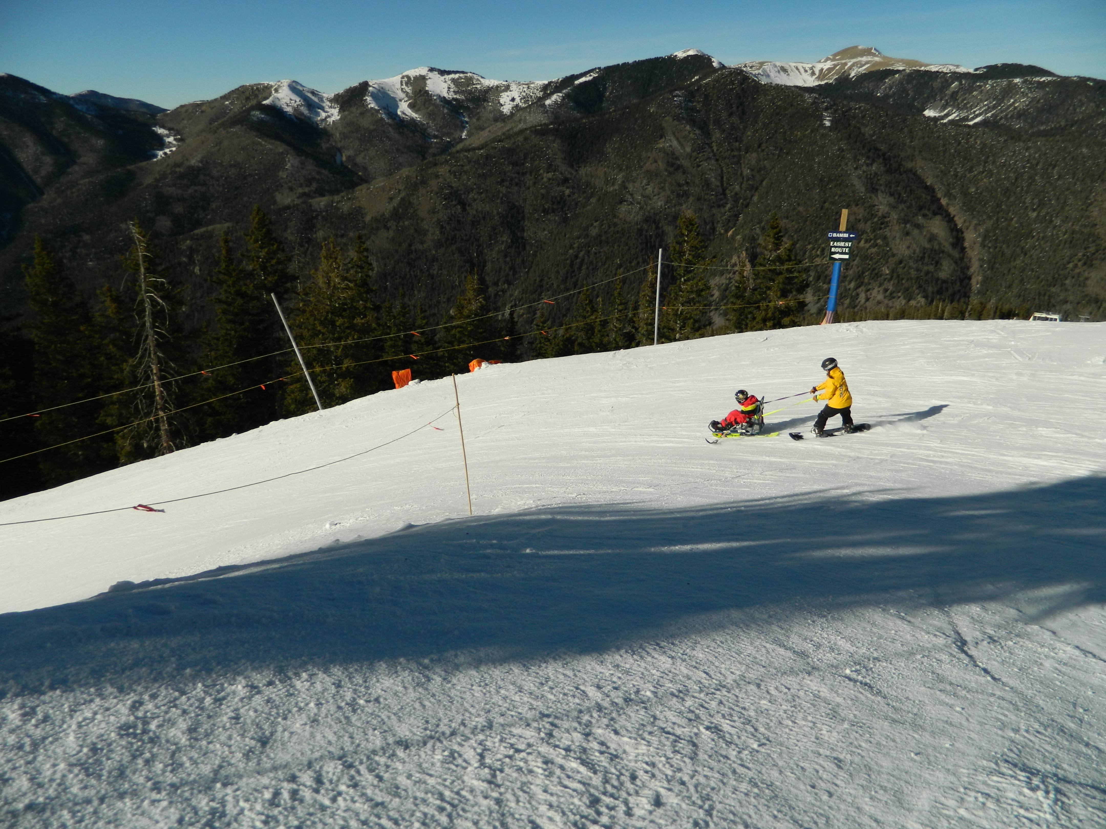 A snowboarder holds onto ropes attached to a disabled skier in a ski chair as they slide downhill. Mountain peaks behind.