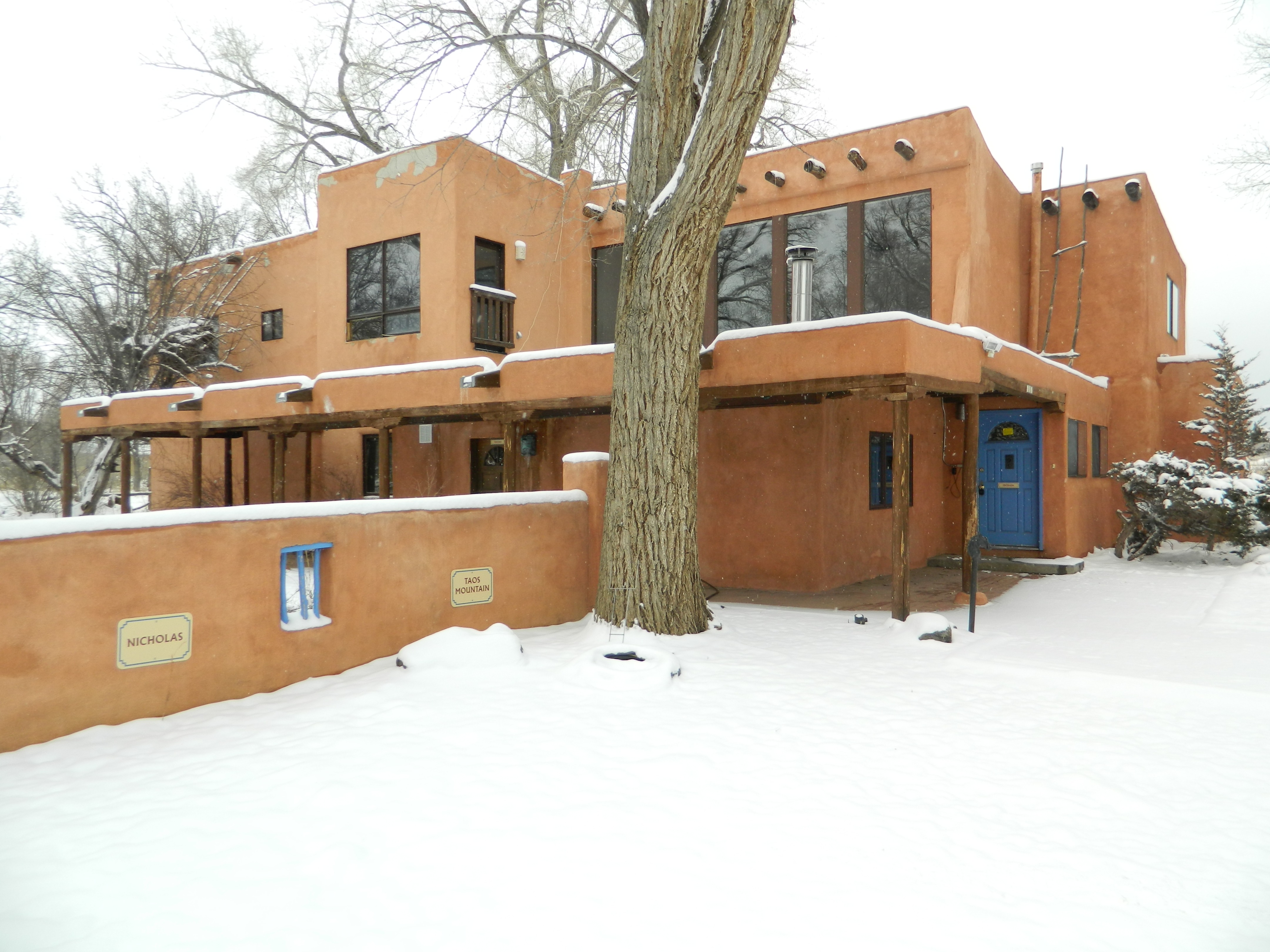 Not Forgotten Outreach Respite Center, a large, pueblo-style building with blue door, on a snowy day