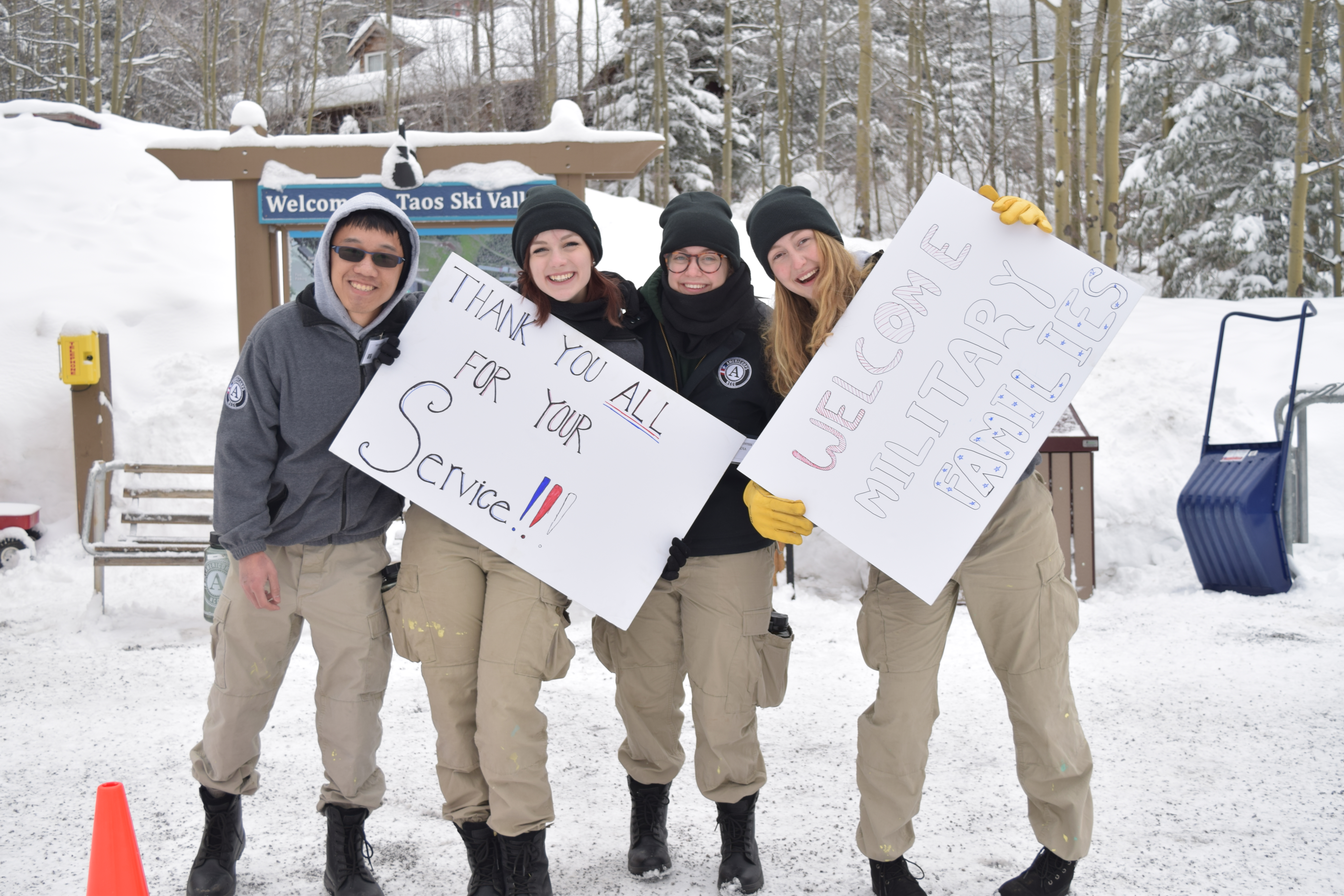 Four young adults in cargo pants and black boots at Taos Ski Valley holding signs welcoming and thanking military families.