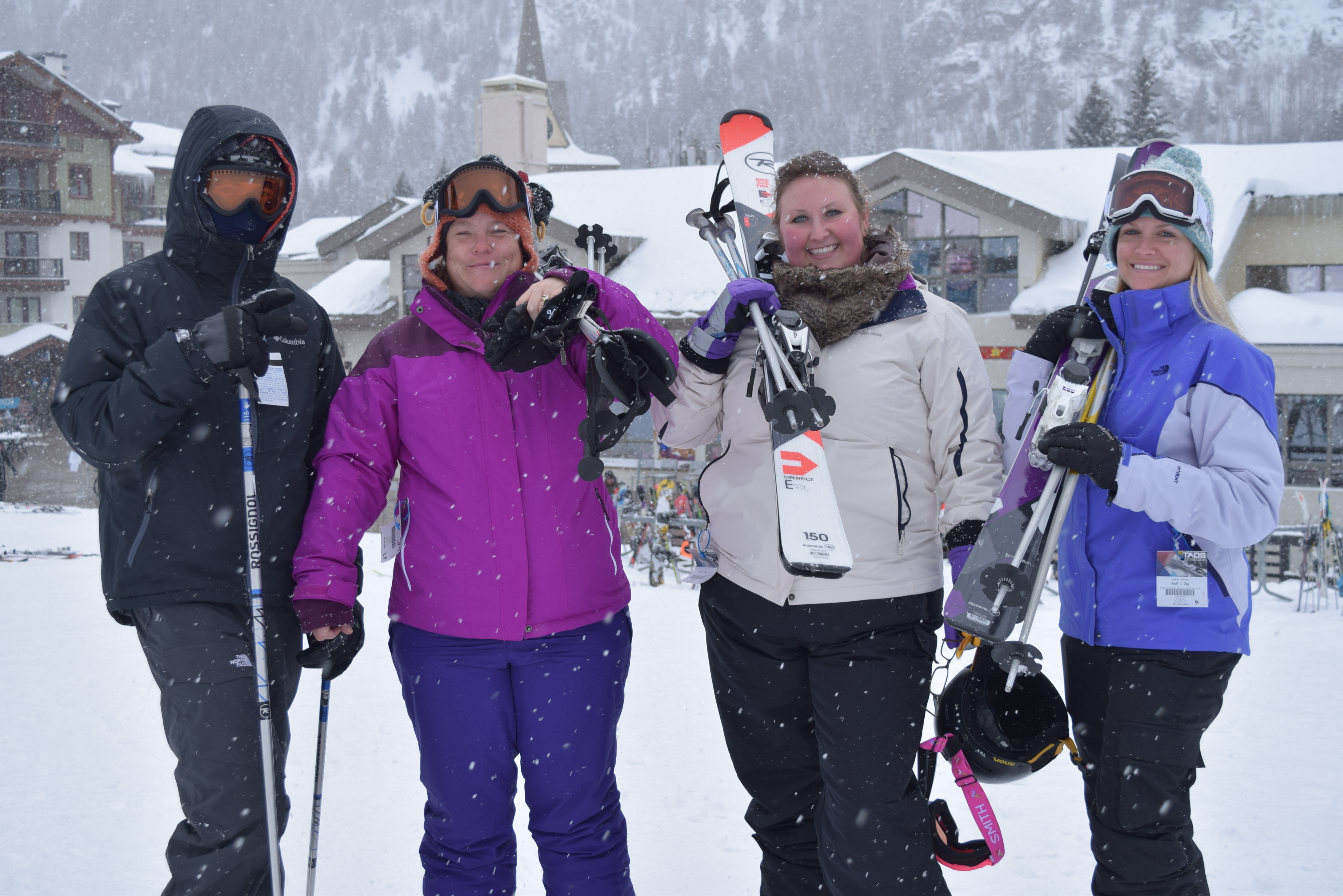 Four skiers pose side-by-side on a snowy day at Taos Ski Valley, lodge in background