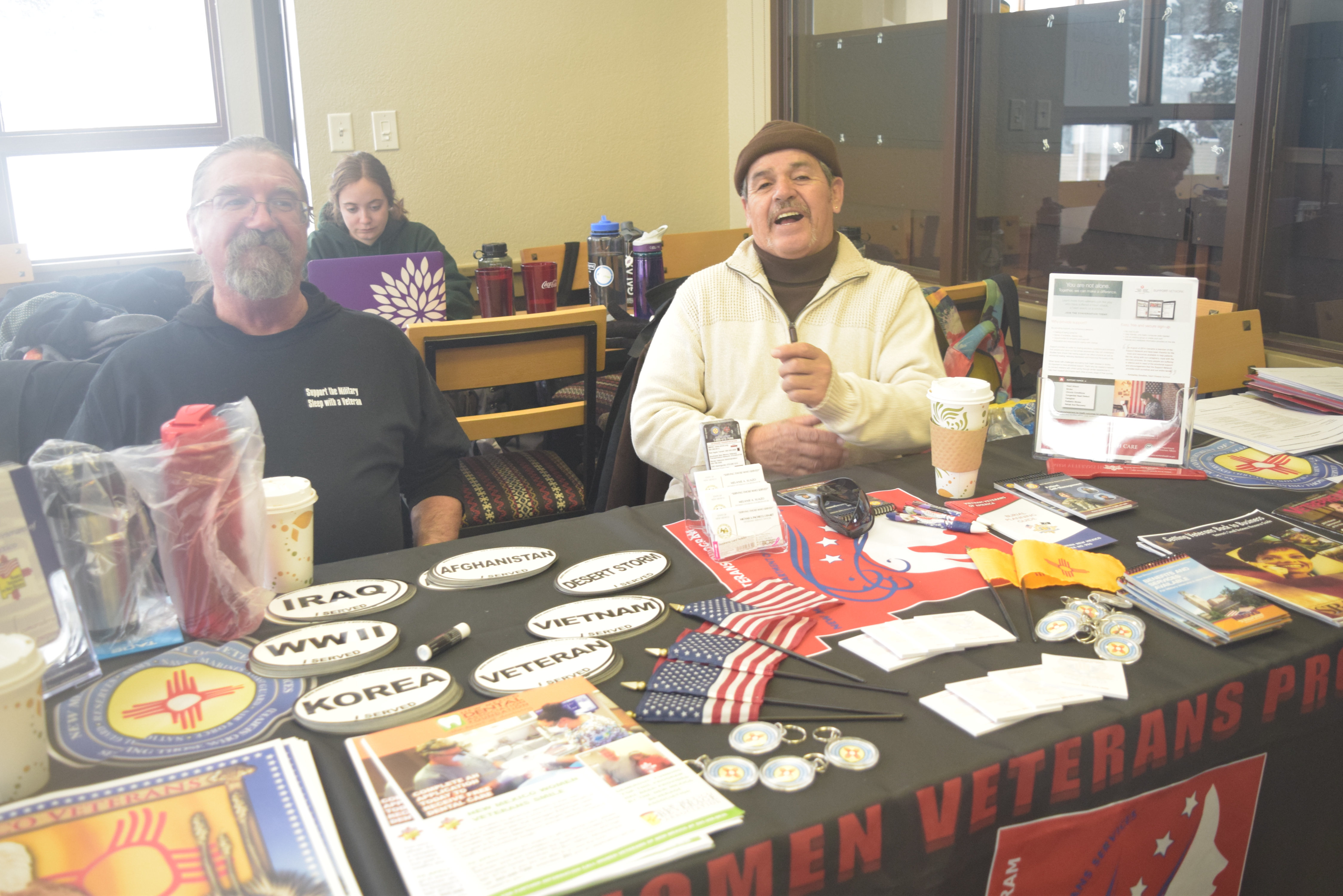 Two cheerful men sit behind a table with veteran brochures, patches, bumper stickers, keychains, and flags
