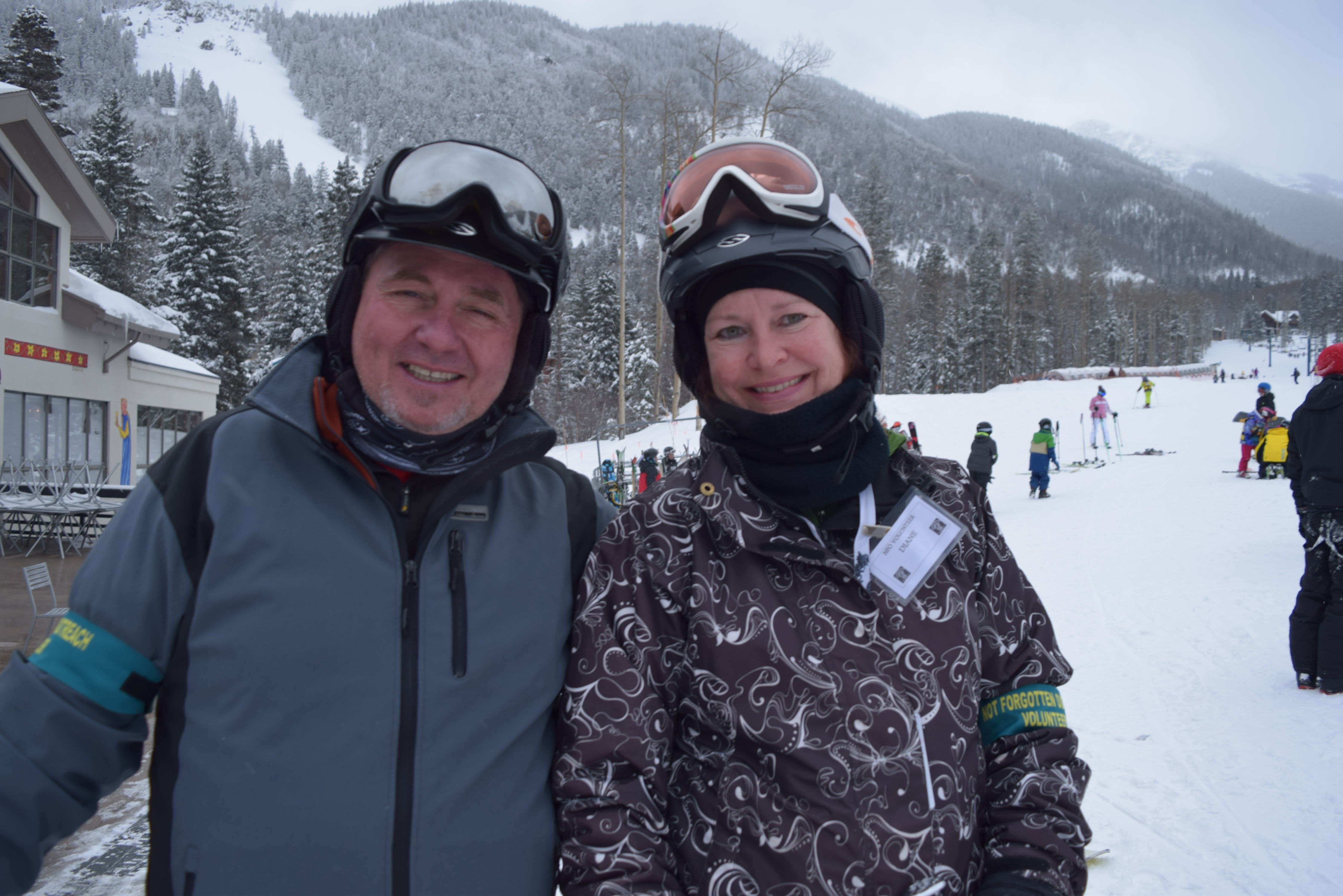 Two skiers, a man and a woman, embrace side-by-side under overcast skies. Lodge, wintry mountains, and skiers in background.
