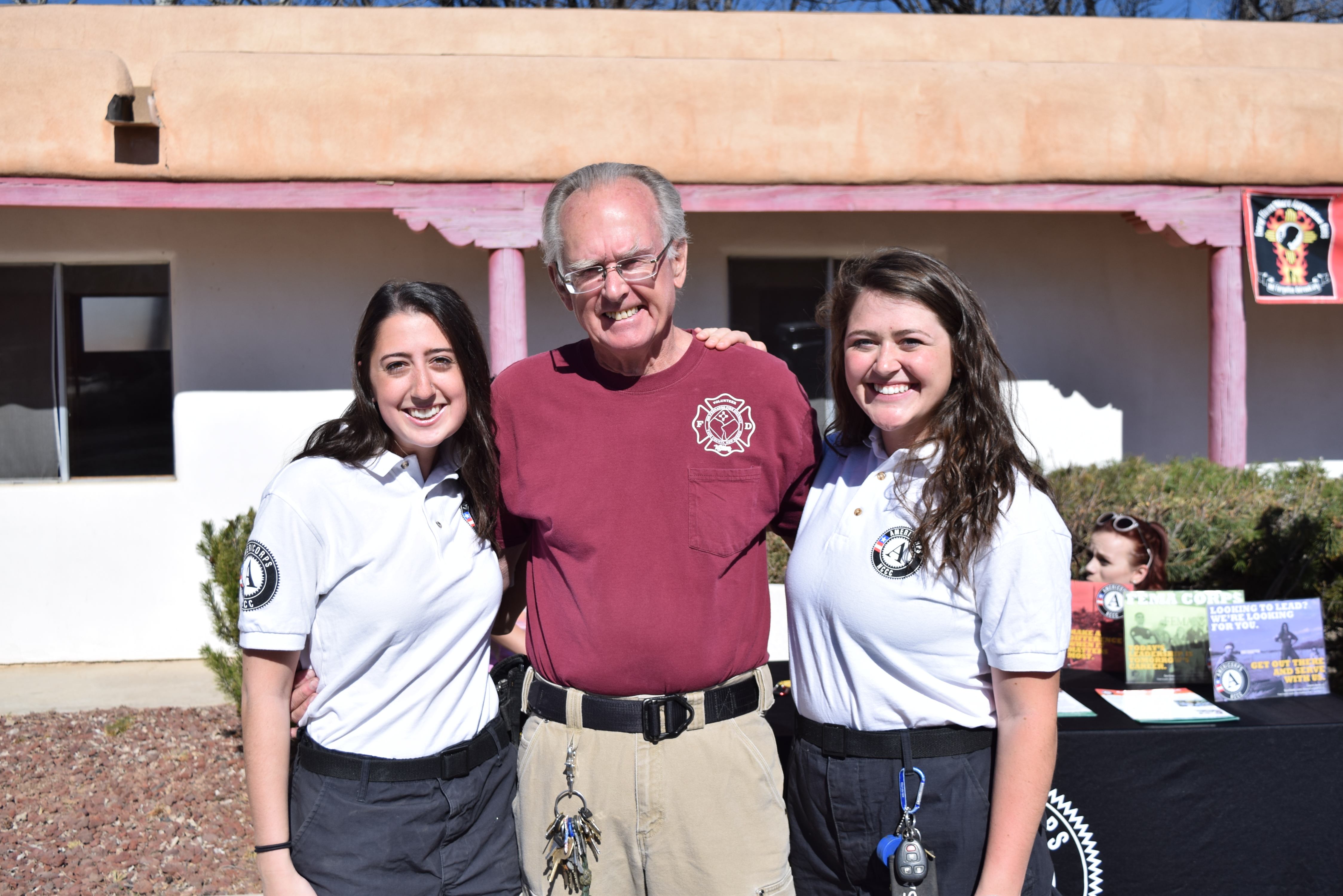 Elder wearing firefighter T-shirt standing outside between two young Americorps volunteers, embracing them side by side