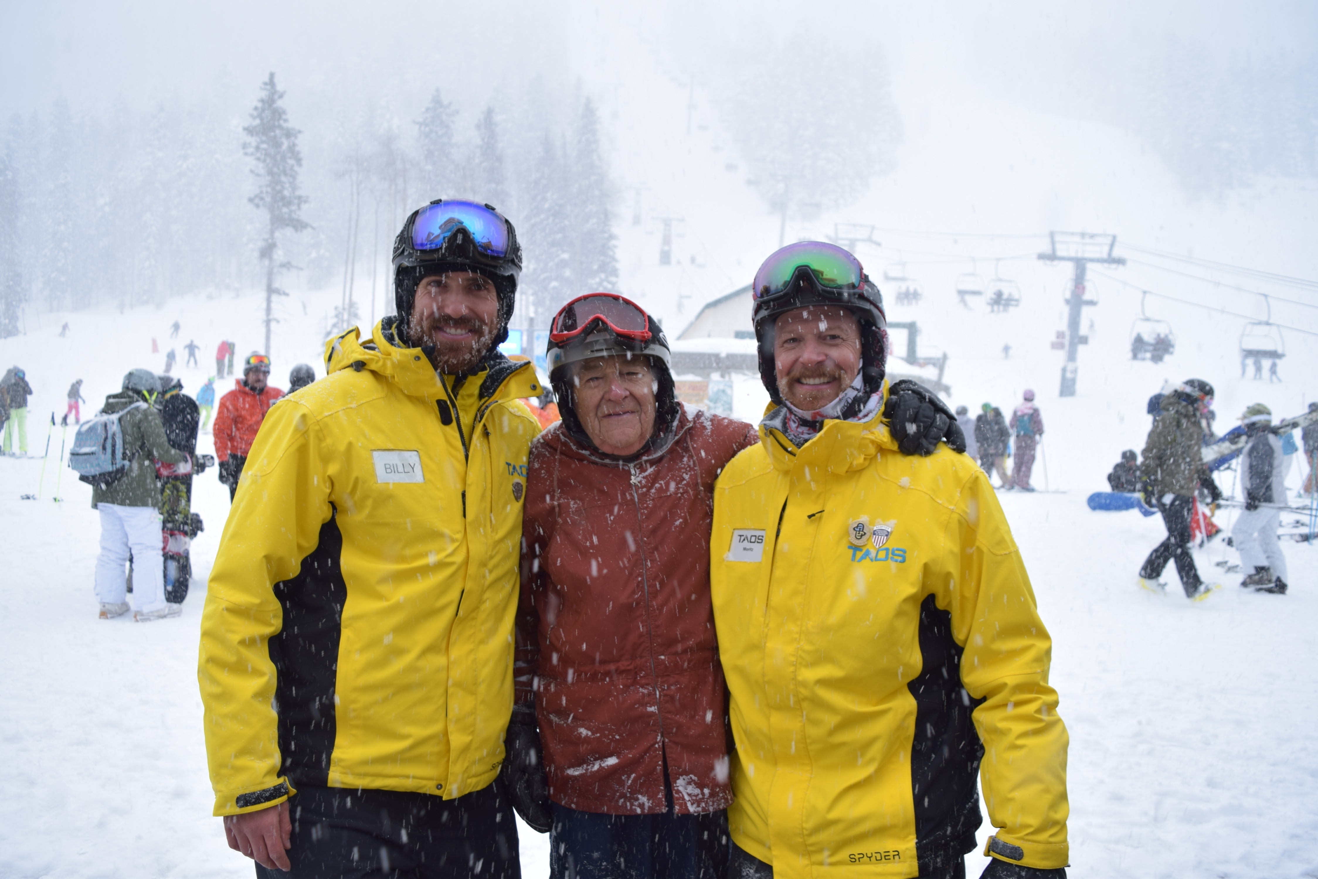 A older skier embraces two Taos Ski Valley instructors. Chairlift, skiers, and snowboarders in background. Snowing heavily.