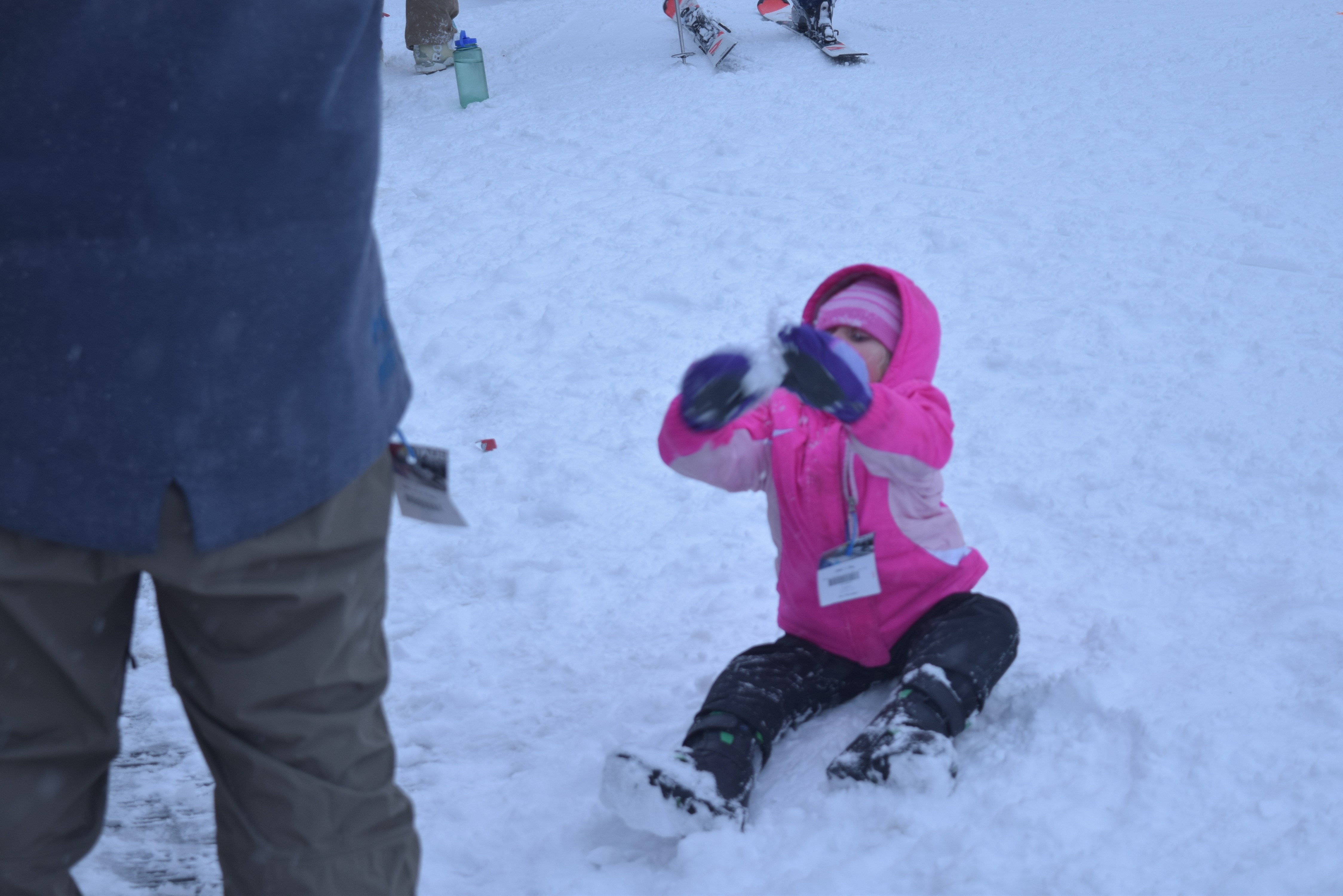 Child skier in pink coat and hat plays in the snow, other skiers standing around