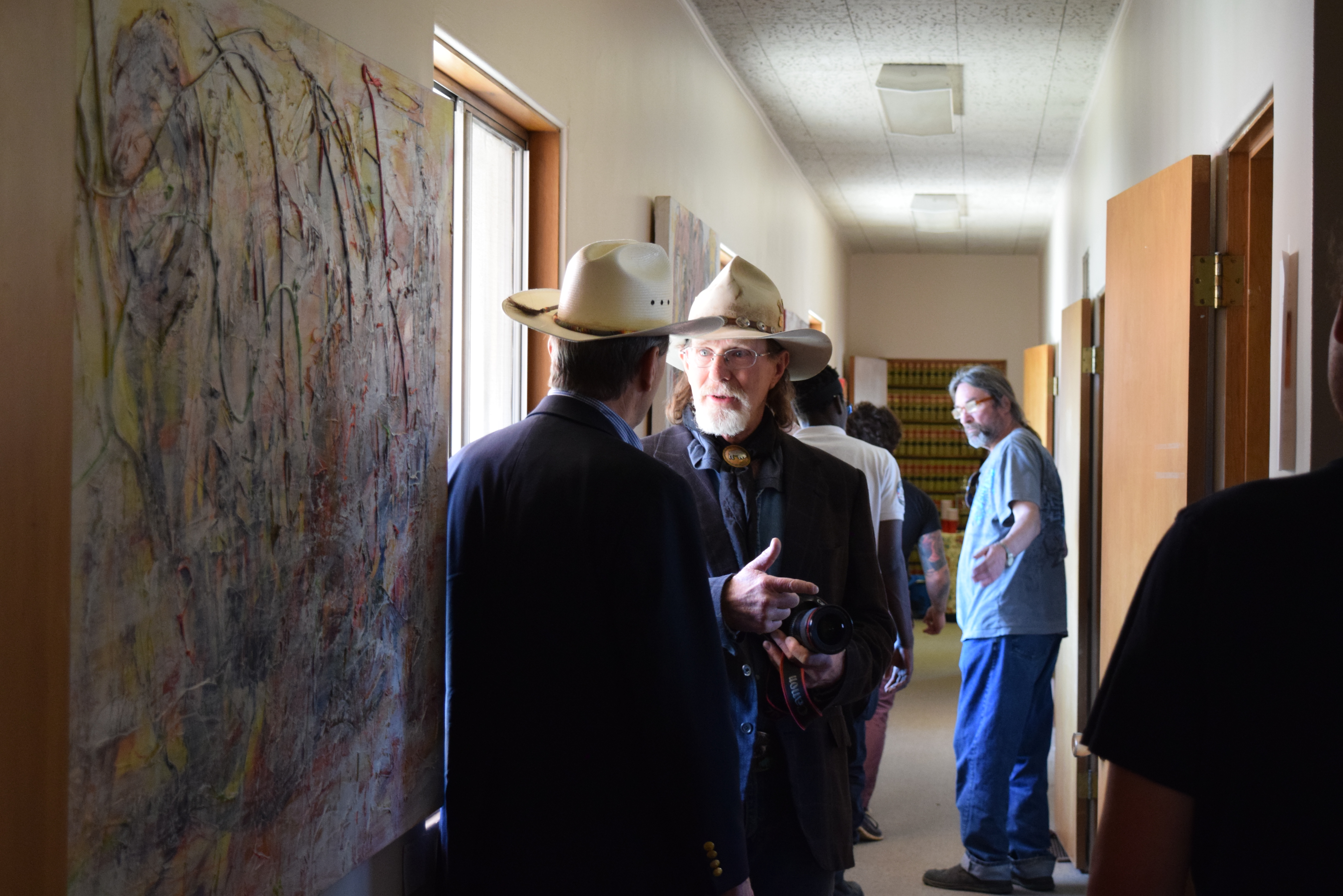 Senator Tom Udall conversing with a bearded man, both wearing straw Stetson hats and suits, in a busy, narrow hallway