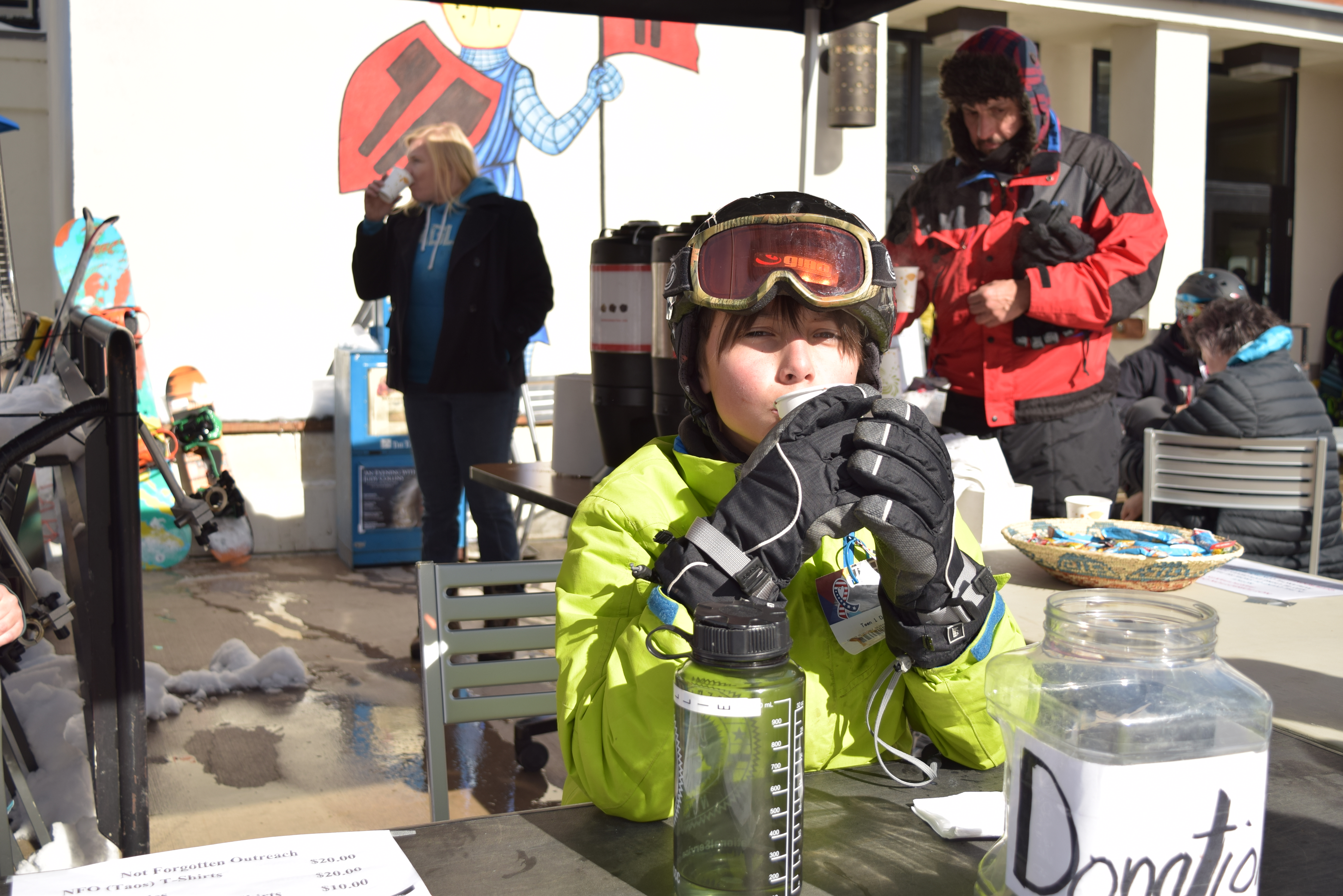 Young skier in bright yellow jacket and gloves sipping a drink at a donation table at Taos Ski Valley, other skiers milling