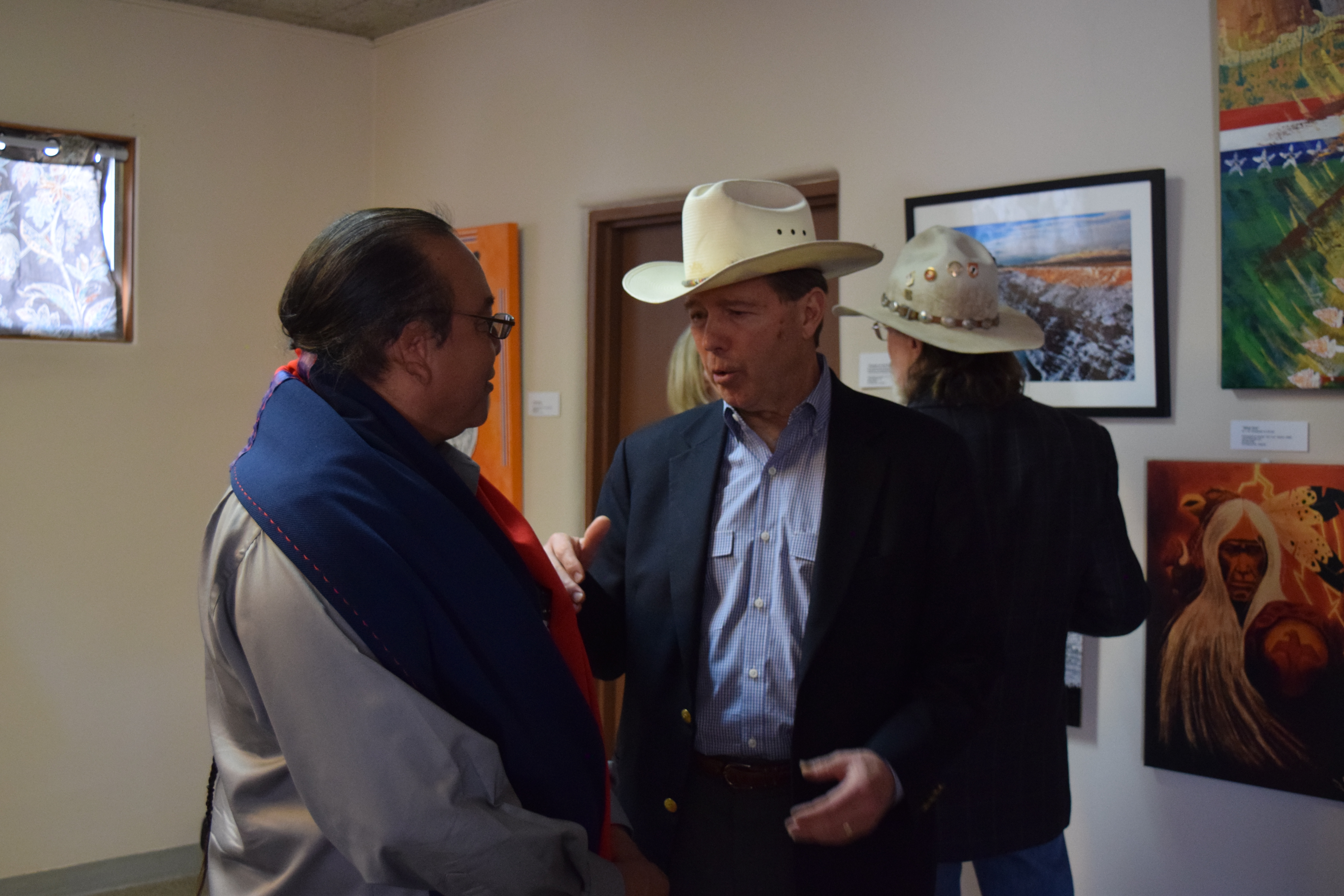 Senator Tom Udall speaking with man wearing large multicolored scarf around his shoulders inside a gallery, others behind