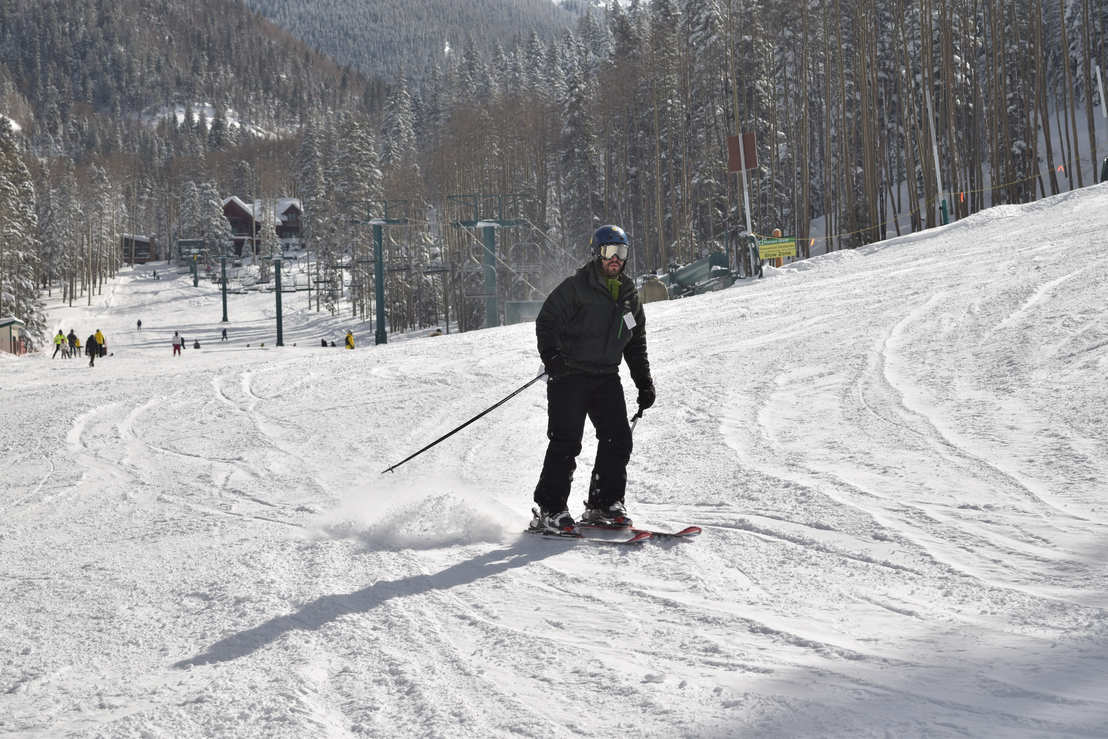 Skier with helmet and goggles carving in from off the slope, chairlift poles, lodge, and snowy forest in the background