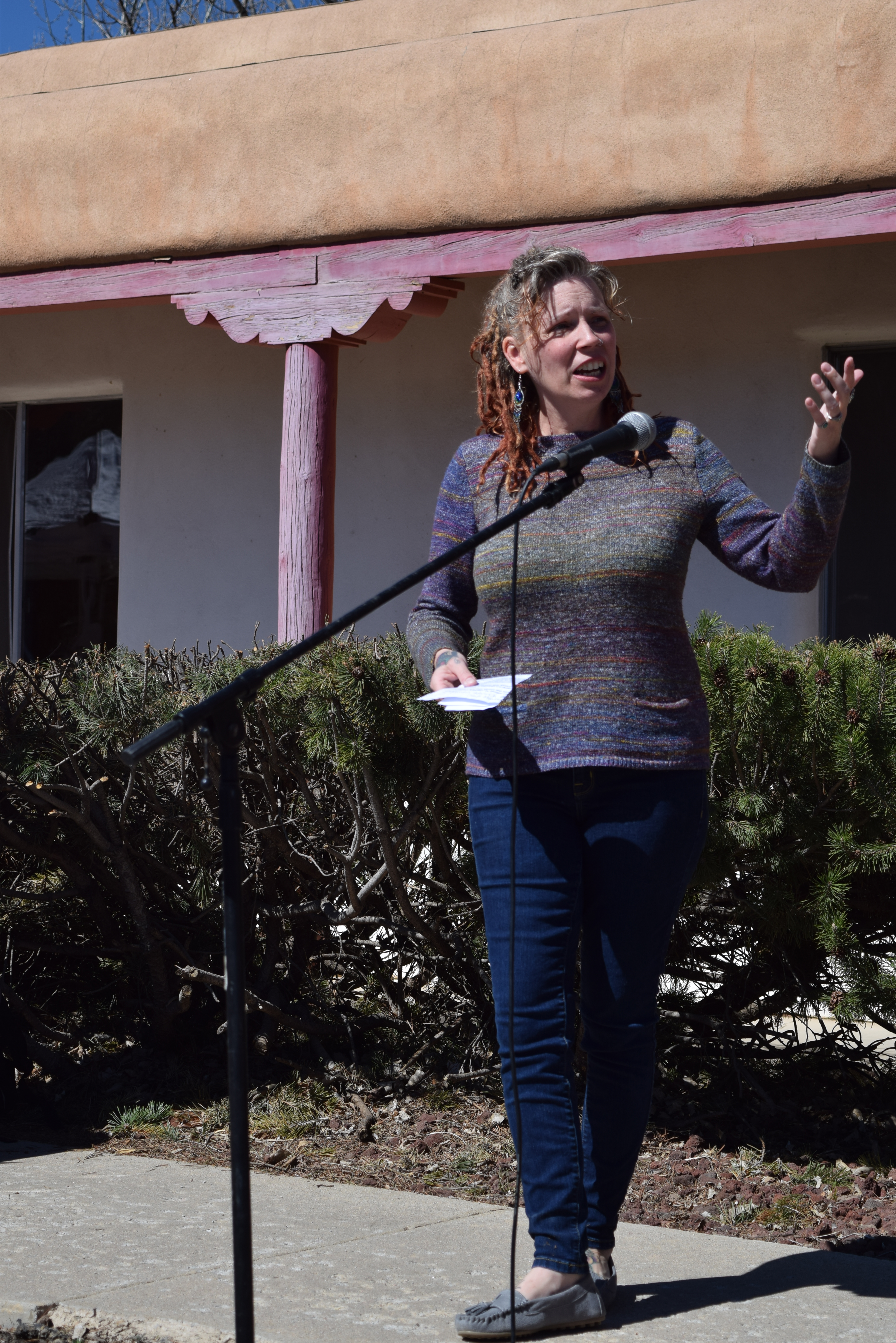 Woman standing and presenting in front of a microphone outside, gesturing with one hand, holding notes with the other
