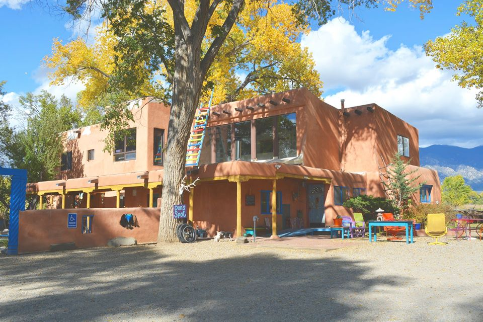 Not Forgotten Outreach Respite Center, a large, colorful, pueblo-style building, under autumn foliage and partly cloudy skies