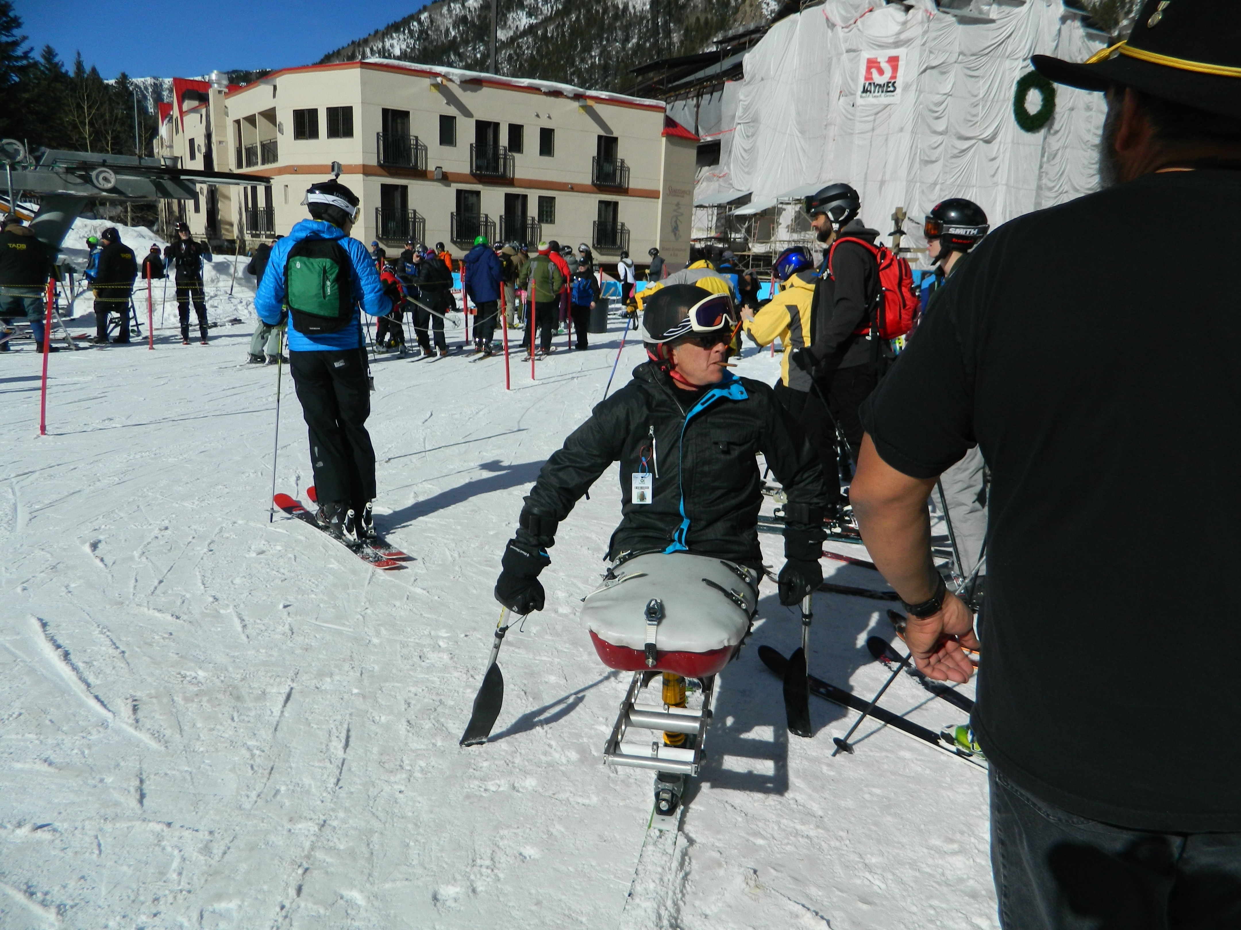 Disabled skier in ski chair at Taos Ski Valley amidst crowd of skiers milling around entrance to chairlift. Lodges behind.