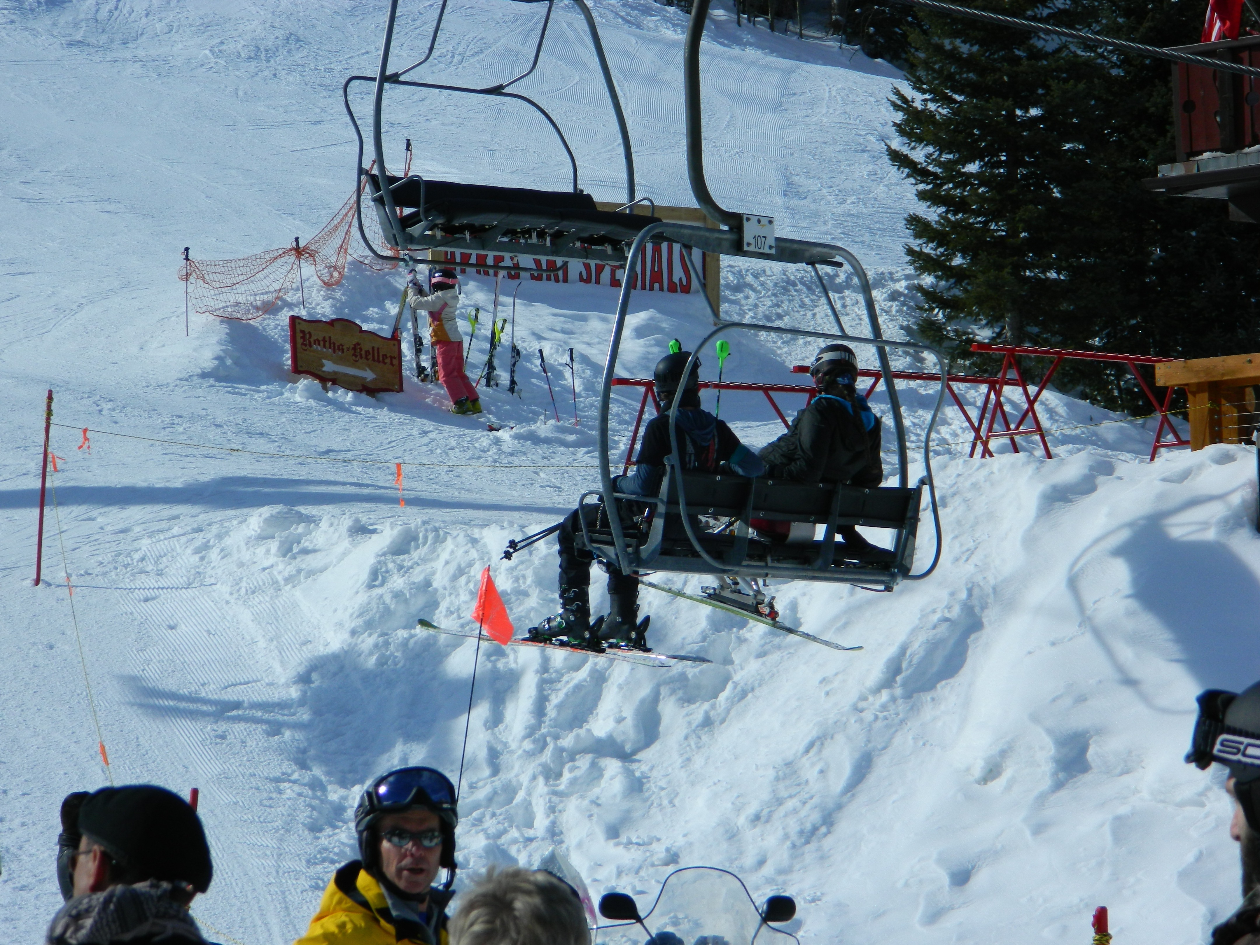 A disabled skier in a ski chair and companion ride a chairlift near the base of Taos Ski Valley on a sunny day.
