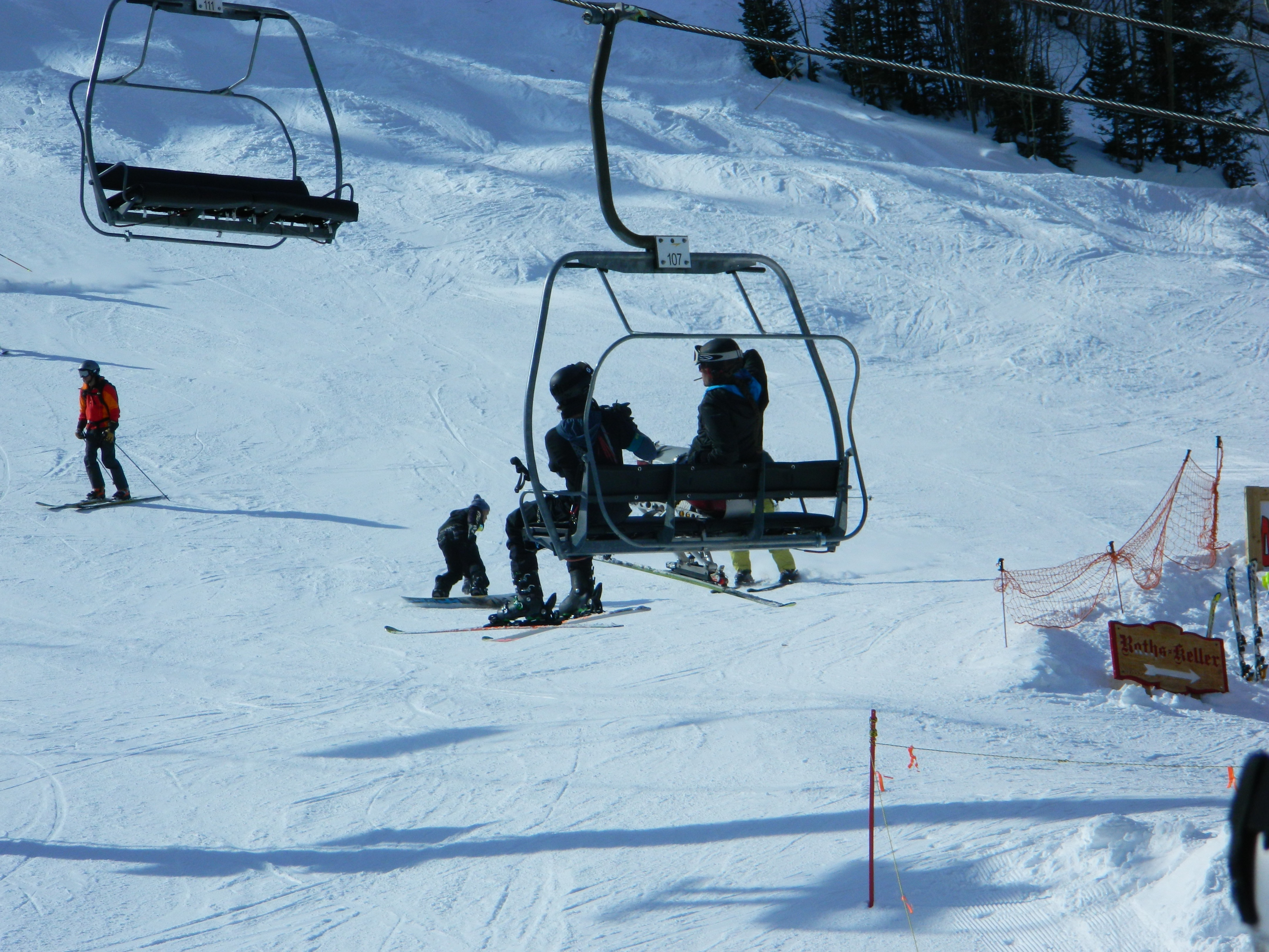 A disabled skier in a ski chair and companion ride a chairlift near the base of Taos Ski Valley.