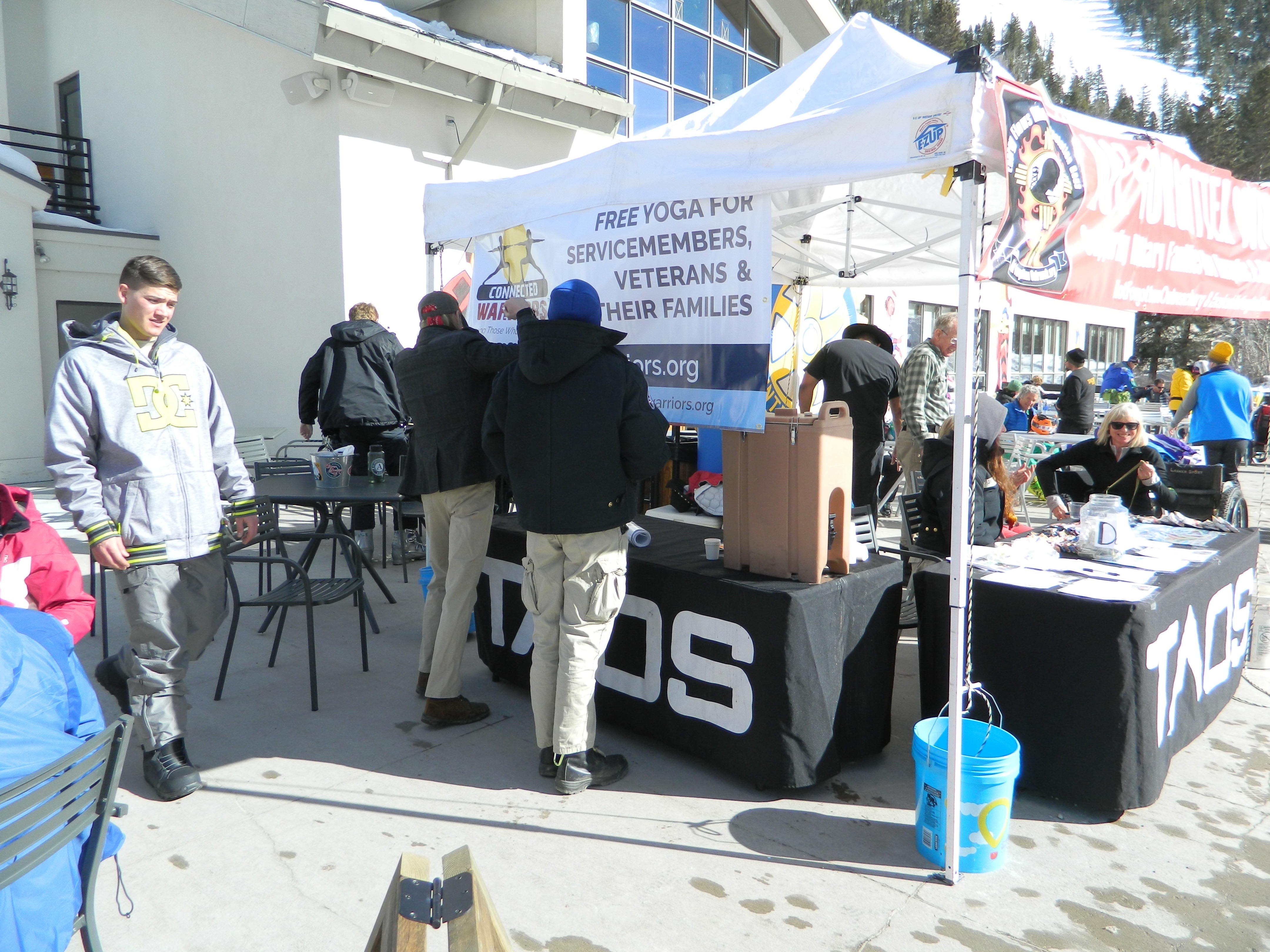"""Not Forgotten Outreach tent at Taos Ski Valley. Banner: """"Free yoga for servicemembers, veterans, & their families."""""""