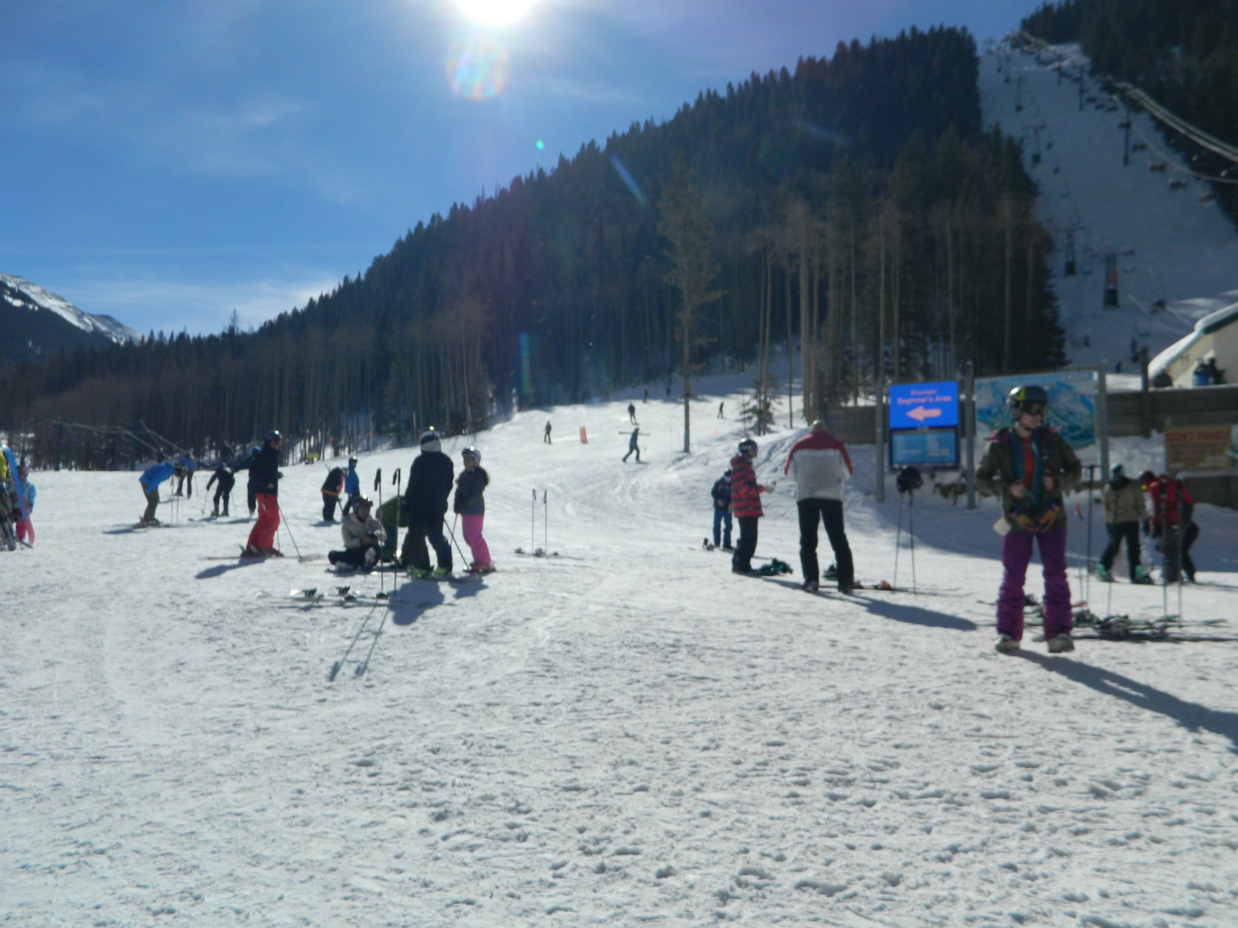 Sun and lens flare looking up at steep chairlift run at Taos Ski Valley. Skiers milling about and preparing.