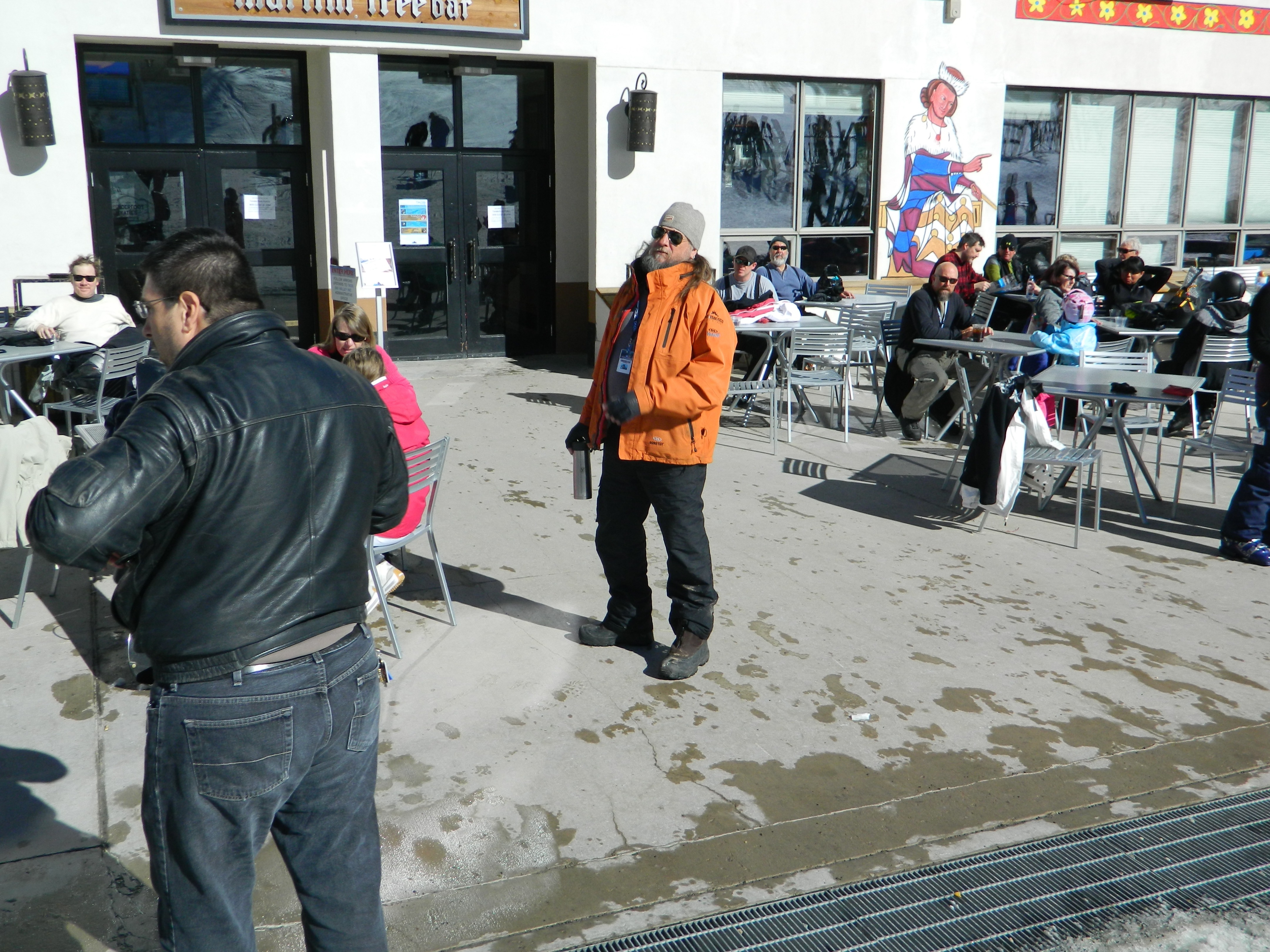 A man in an orange jacket standing on the patio in front of Tenderfoot Katie's at Taos Ski Valley. Others relaxing behind.