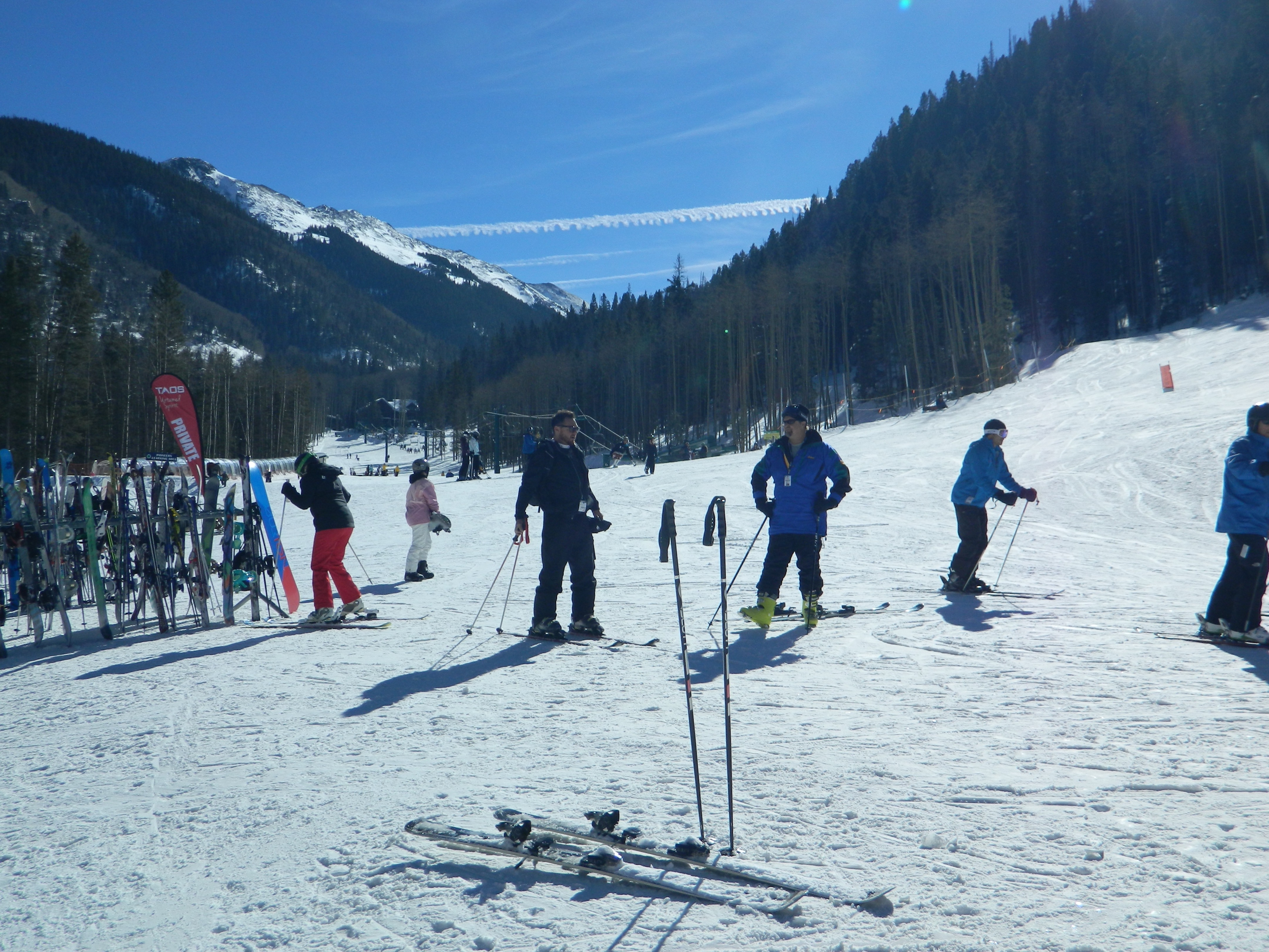 A pair of skis and poles by themselves at the base of Taos Ski Valley. Skiers, wintry forest, mountain peaks, blue skies.