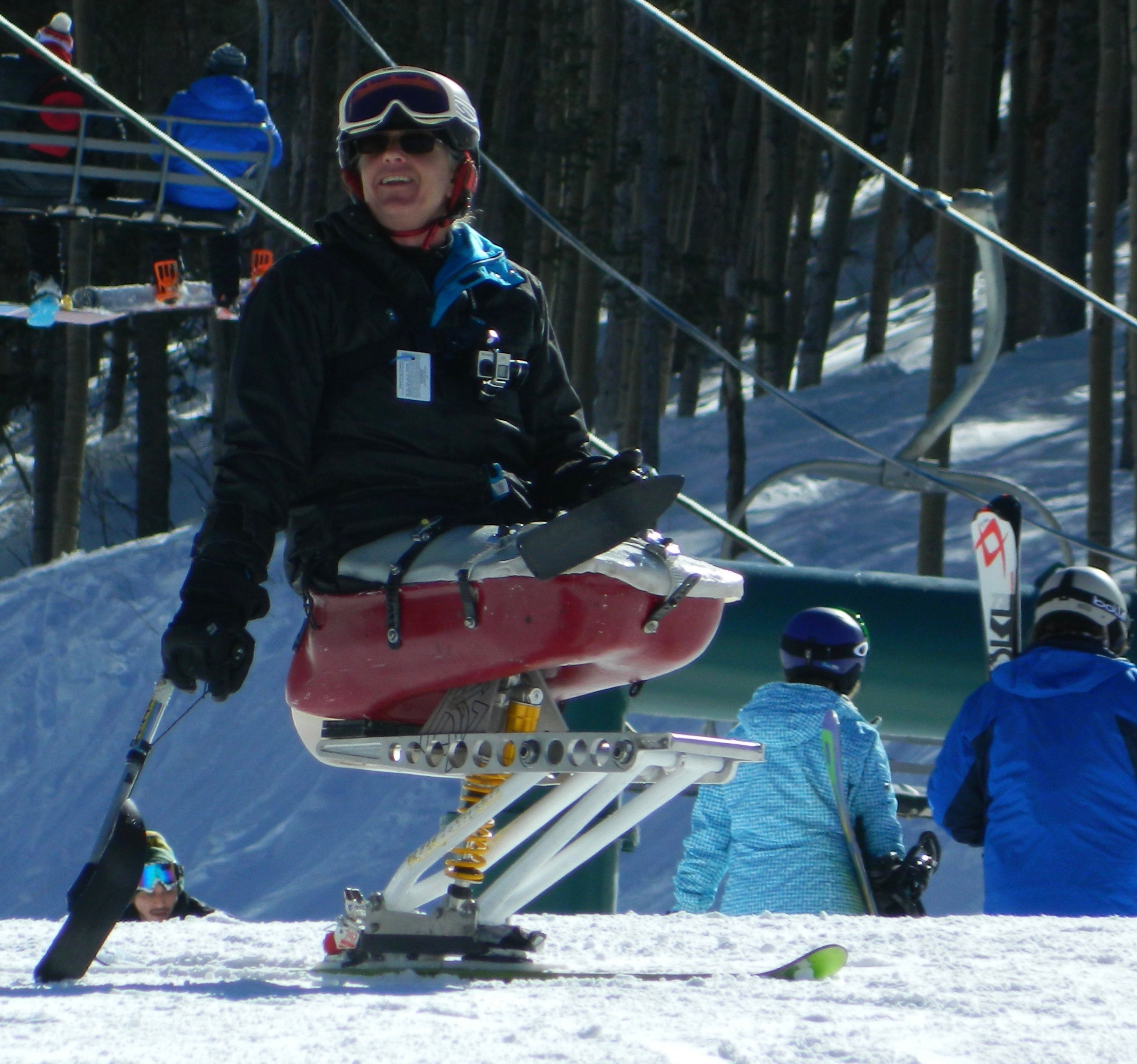 Cheerful disabled skier in red ski chair at Taos Ski Valley. Skiers, chairlift, and wintry forest in the background.