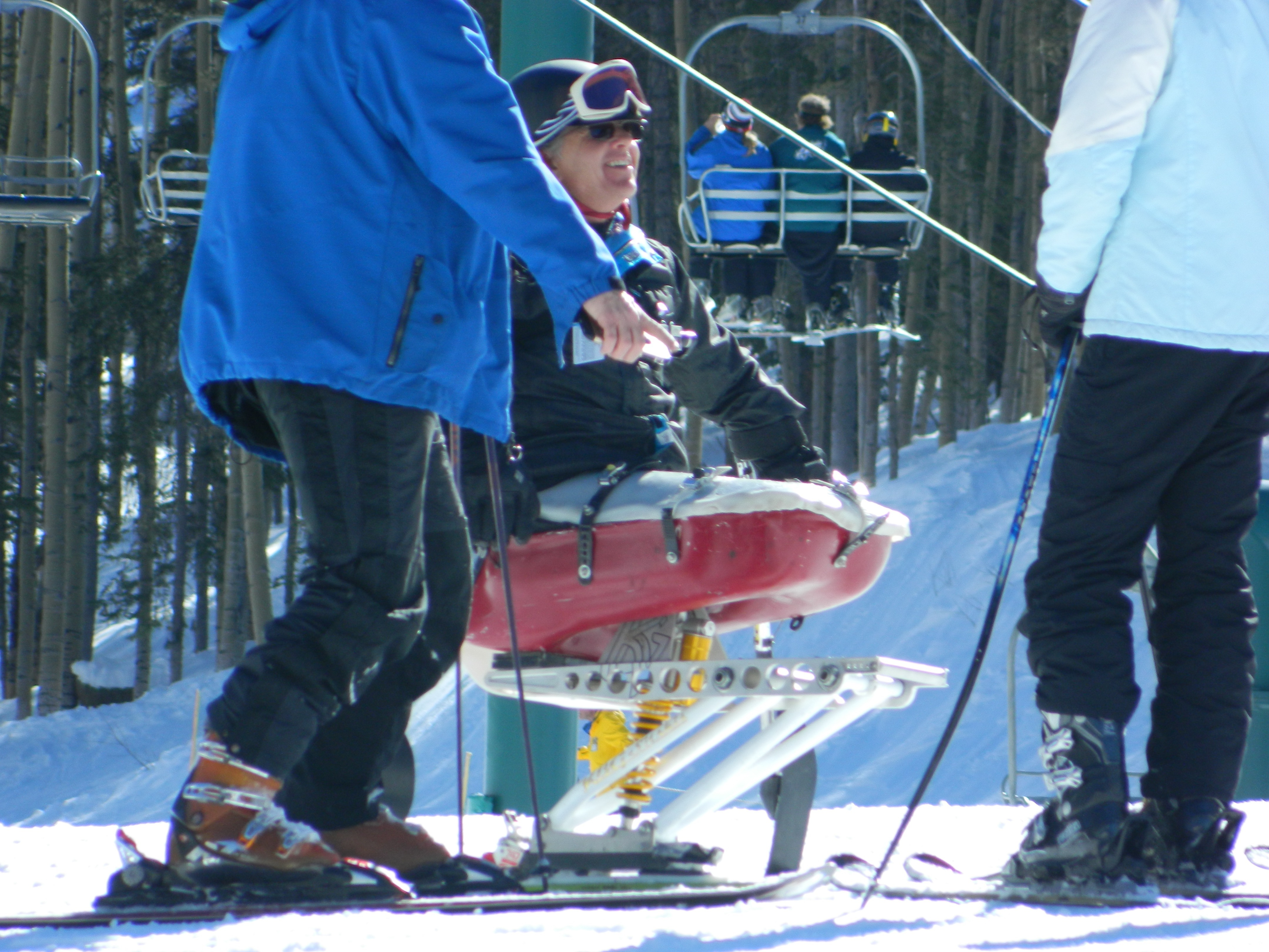 Cheerful disabled skier in red ski chair chats with two other skiers. Chairlift and wintry forest behind.