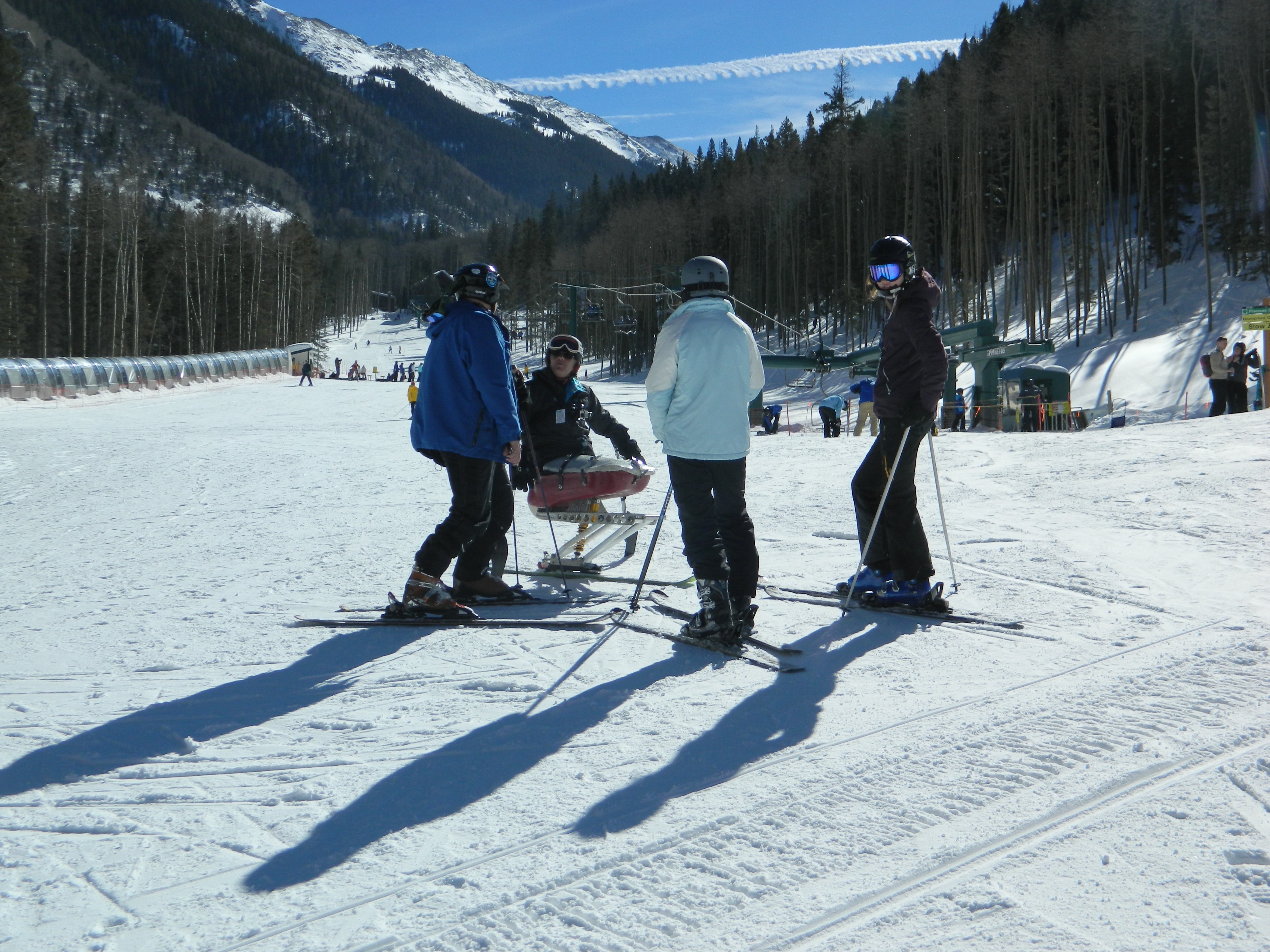 Four skiers, one disabled, confer at the base of Taos Ski Valley. Peaks, wintry forest, skiers, and lodge behind. Blue skies.