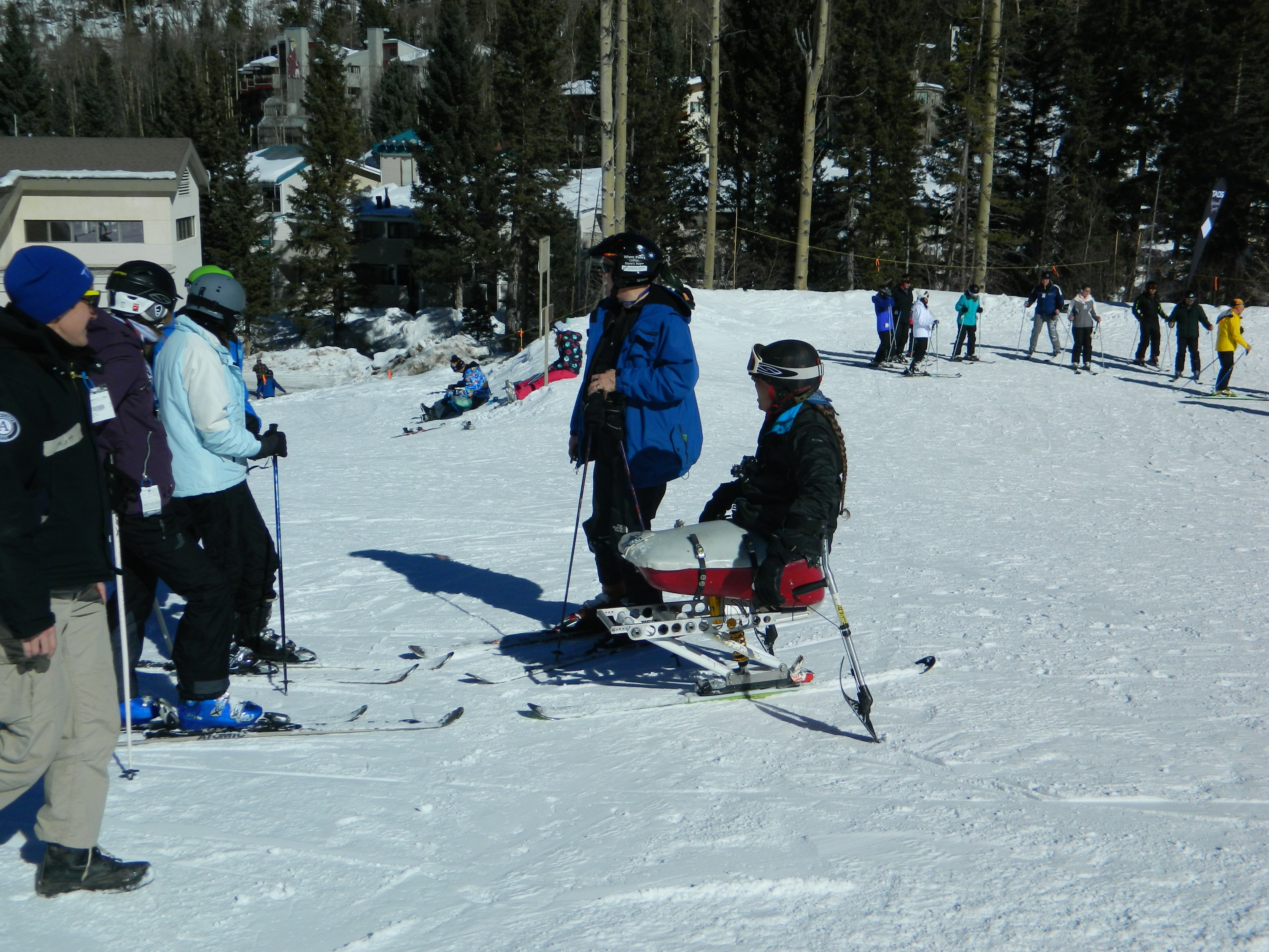 Group of skiers, one disabled, confer on the slopes of Taos Ski Valley. Other skiers behind, and main lodge in the distance.