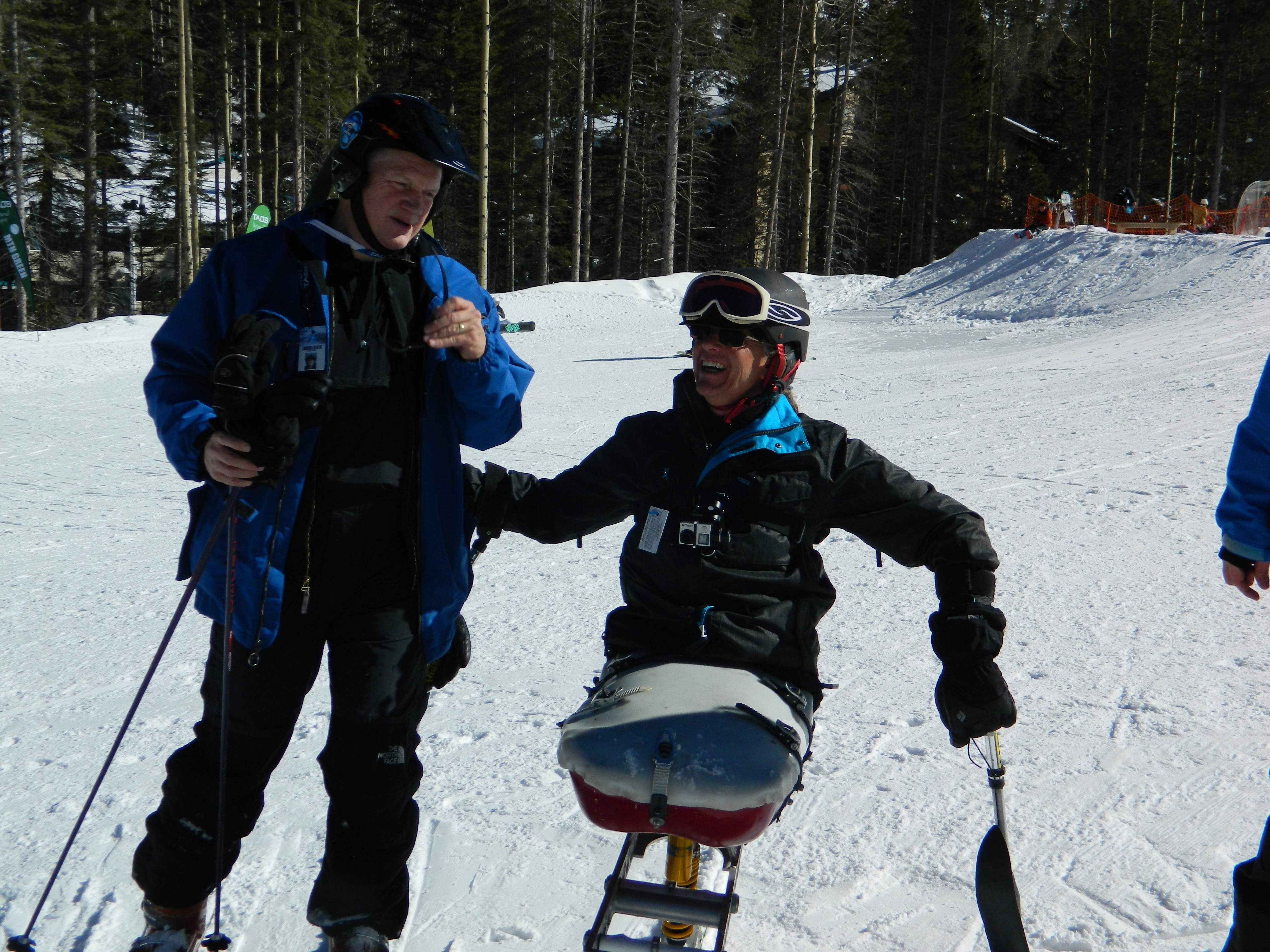 Laughing disabled skier in ski chair jokes with another skier on the slopes at Taos Ski Valley. Wintry forest behind.
