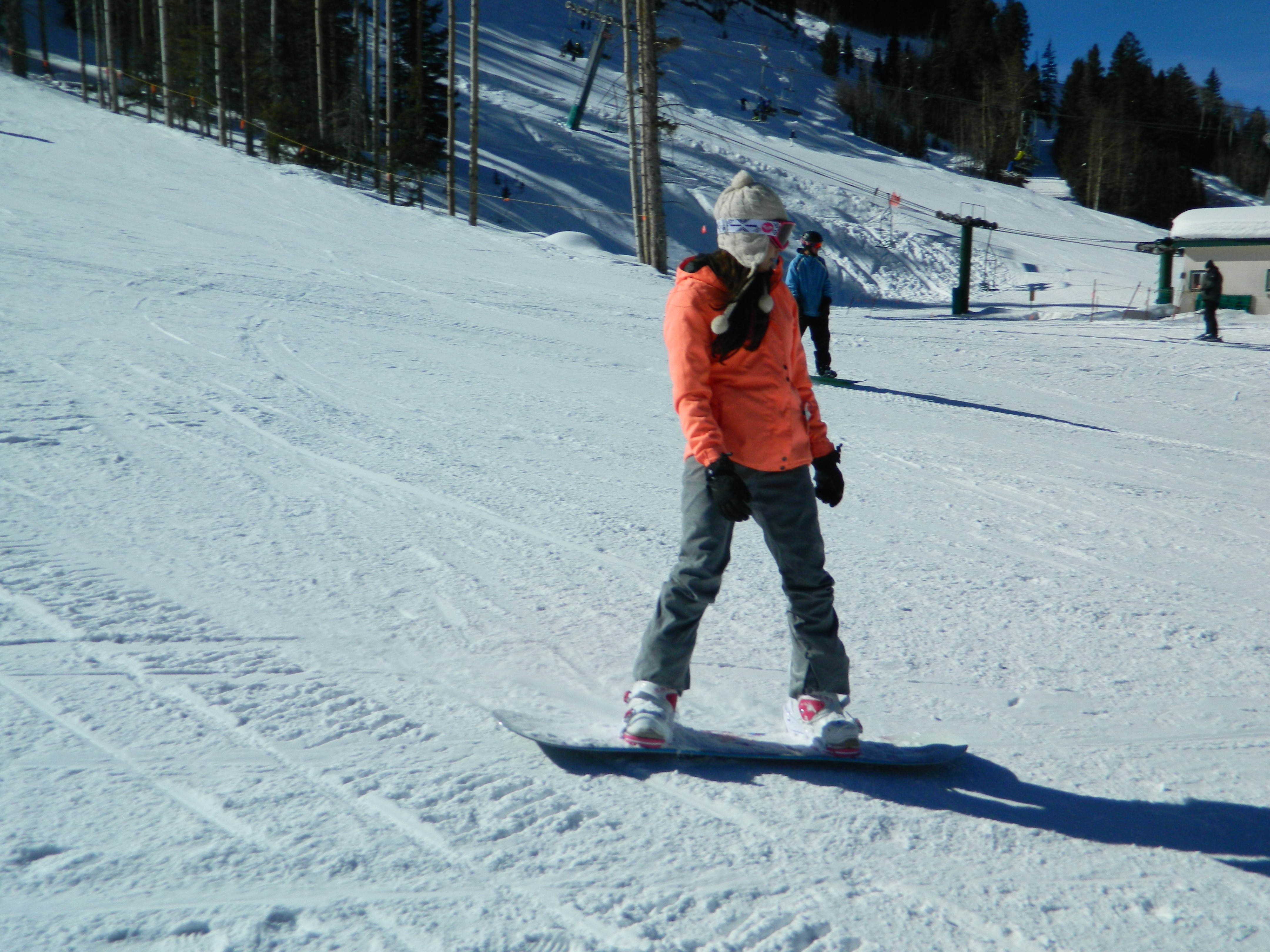 Snowboarder in orange coat slows down at the base of the slope at Taos Ski Valley on a sunny day. Chairlift, skiers behind.
