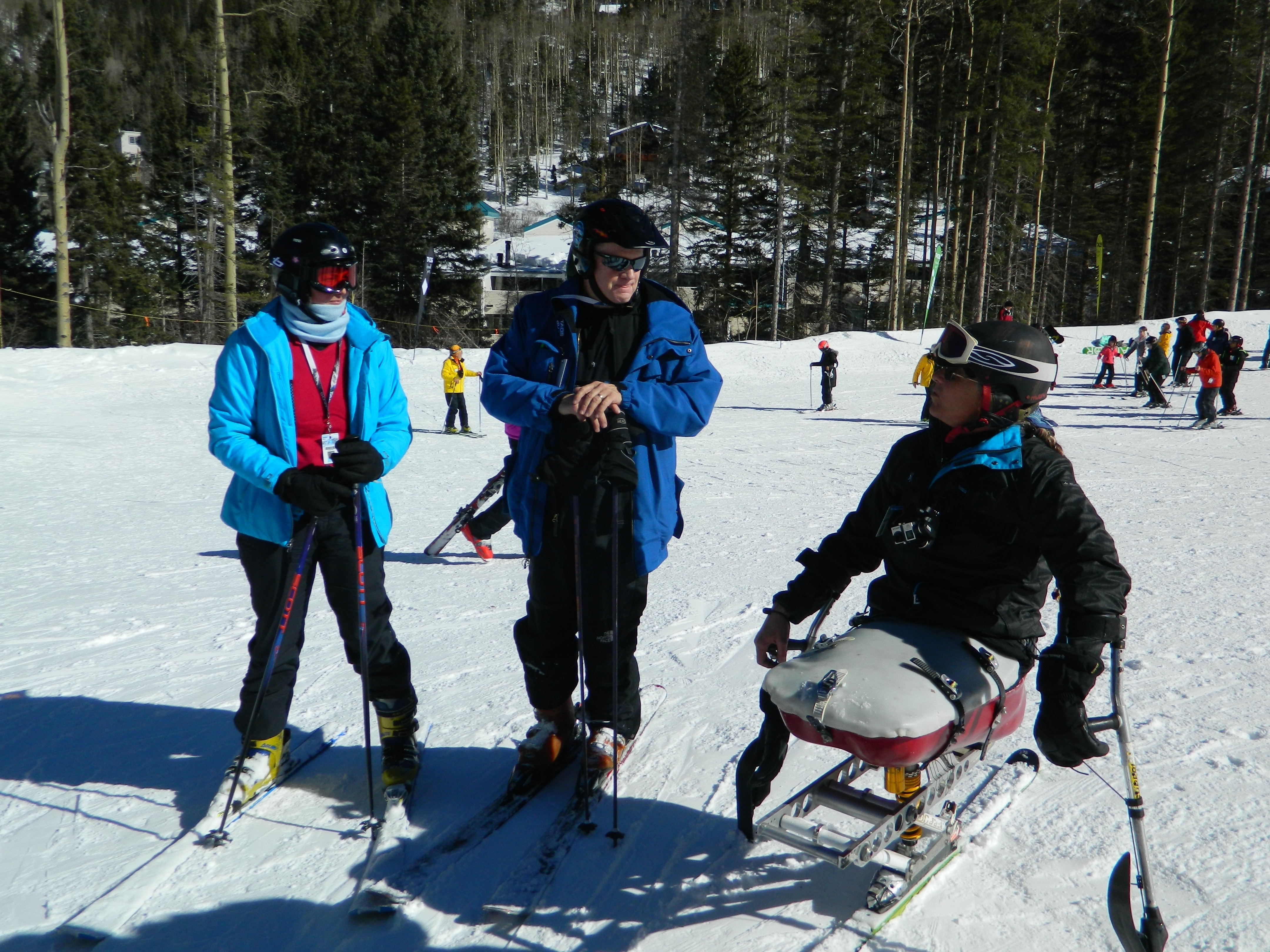 Three skiers, one of them disabled, confer solemnly on the slopes at Taos Ski Valley. Skiers, forest, and lodge behind.