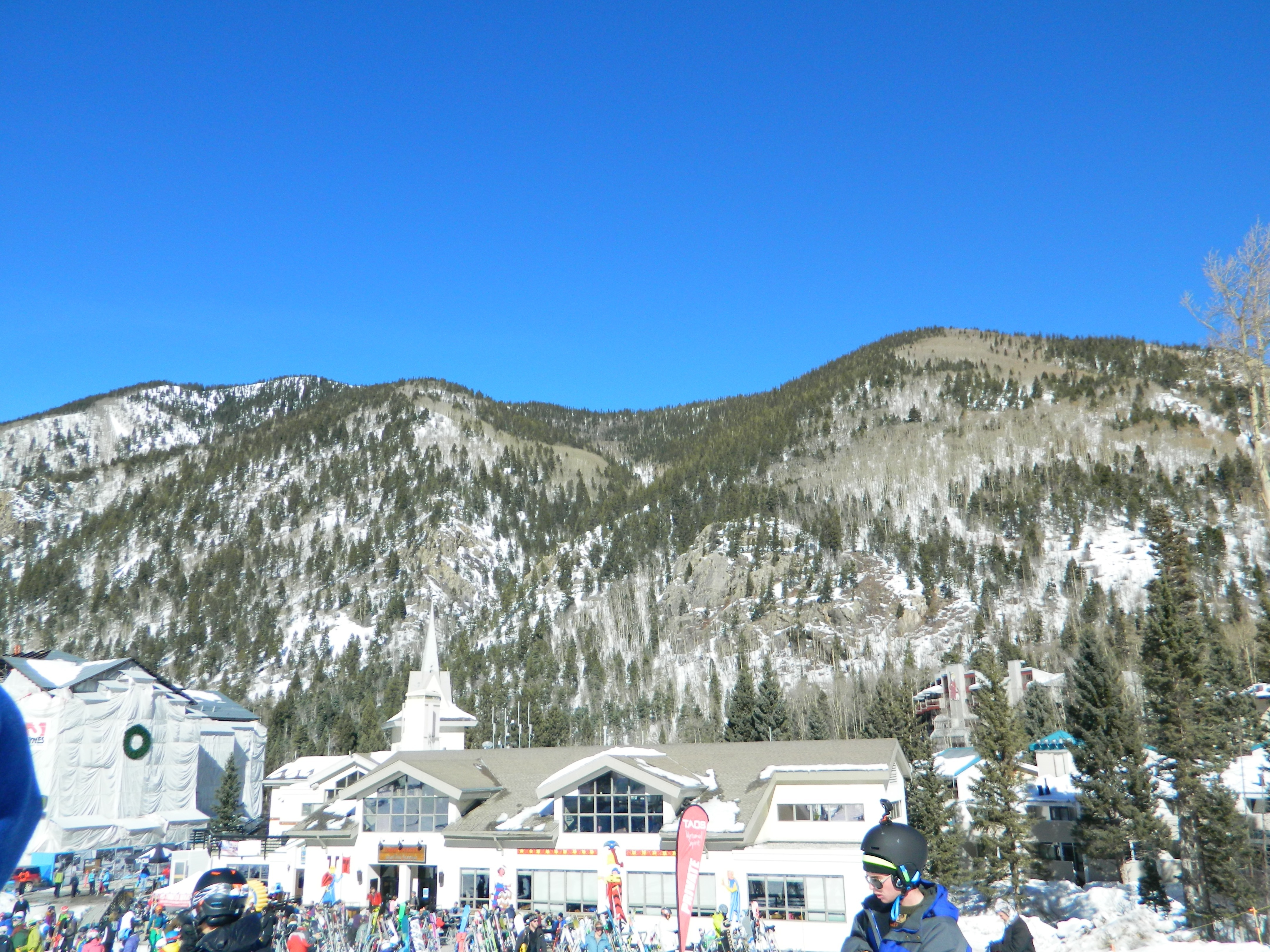 Bright blue sunny day at Taos Ski Valley village, seen from afar. Big crowd of skiers milling near Tenderfoot Katie's patio.