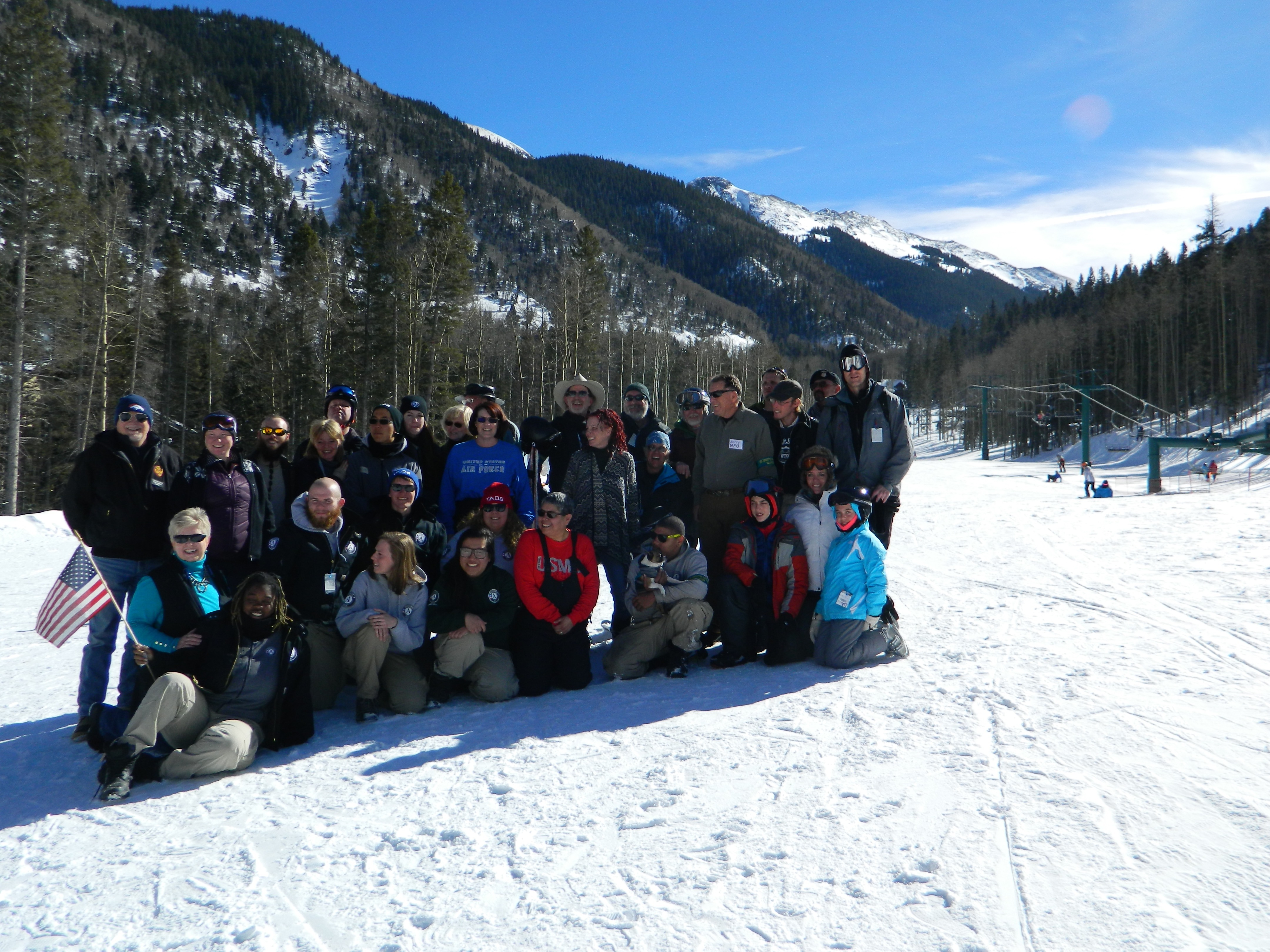 Not Forgotten Outreach group photo at the base of Taos Ski Valley. Chairlift, mountain peaks, blue sky, wintry forest behind.