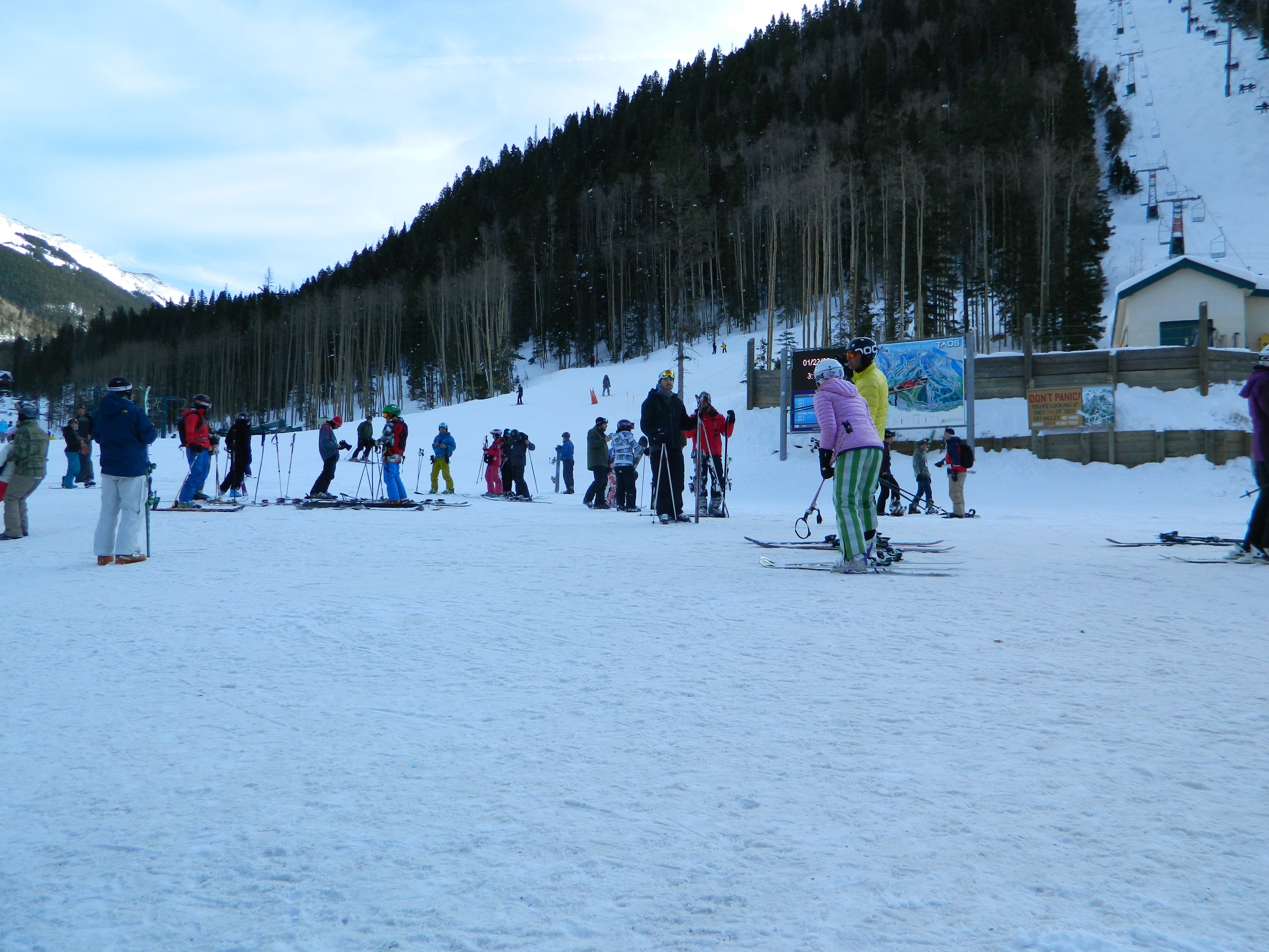 Many skiers conversing at the foot of Taos Ski Valley in the late afternoon shade.