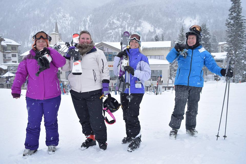Four cheerful skiers at Taos Ski Valley on a snowy day holding their ski equipment over their shoulders. Lodge behind.