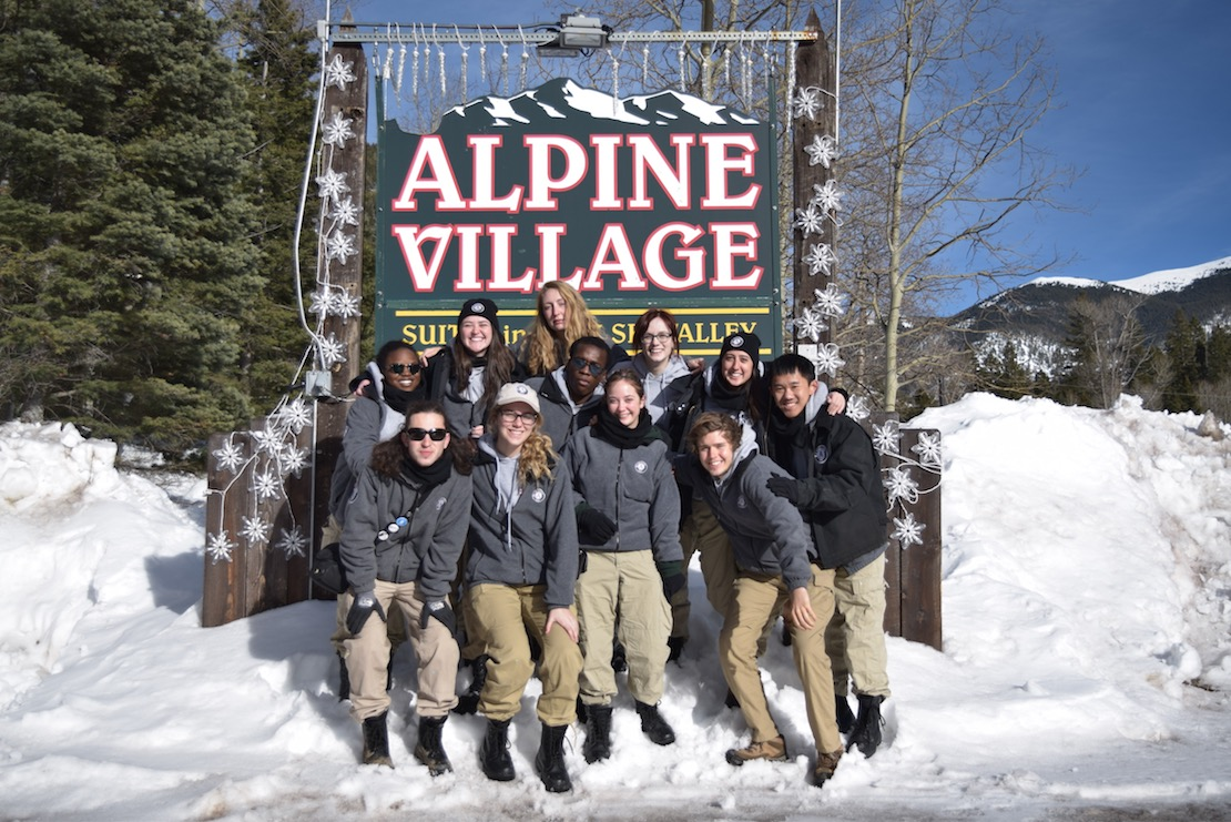 Eleven young adults in two rows posing in the snow bank in front of the Alpine Village sign at Taos Ski Valley, blue skies