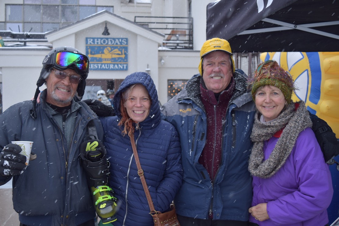 One skier with boots over shoulder joining three others in side-by-side embrace near Rhoda's Restaurant in Taos Ski Valley