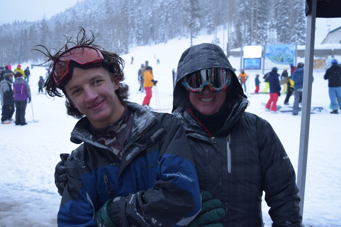 Two happy skiers fresh off the slopes, posing and embracing at cloudy, snowy Taos Ski Valley, other skiers in the background
