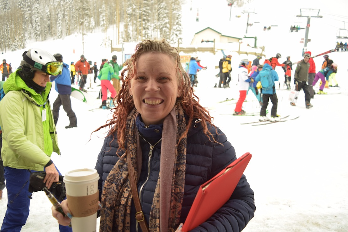 Smiling woman at Taos Ski Valley carrying laptop in bright red case, big Starbucks coffee, and marker, skiers in background