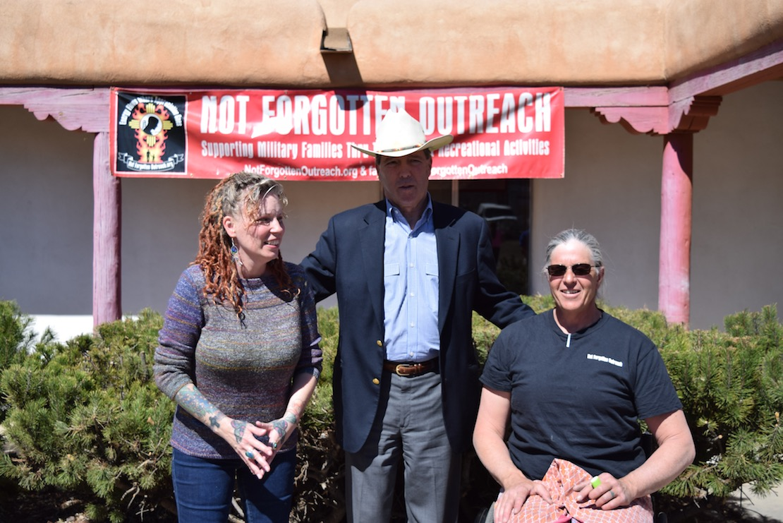 Senator Udall standing between two others outside, embracing them, with a Not Forgotten Outreach banner in the background