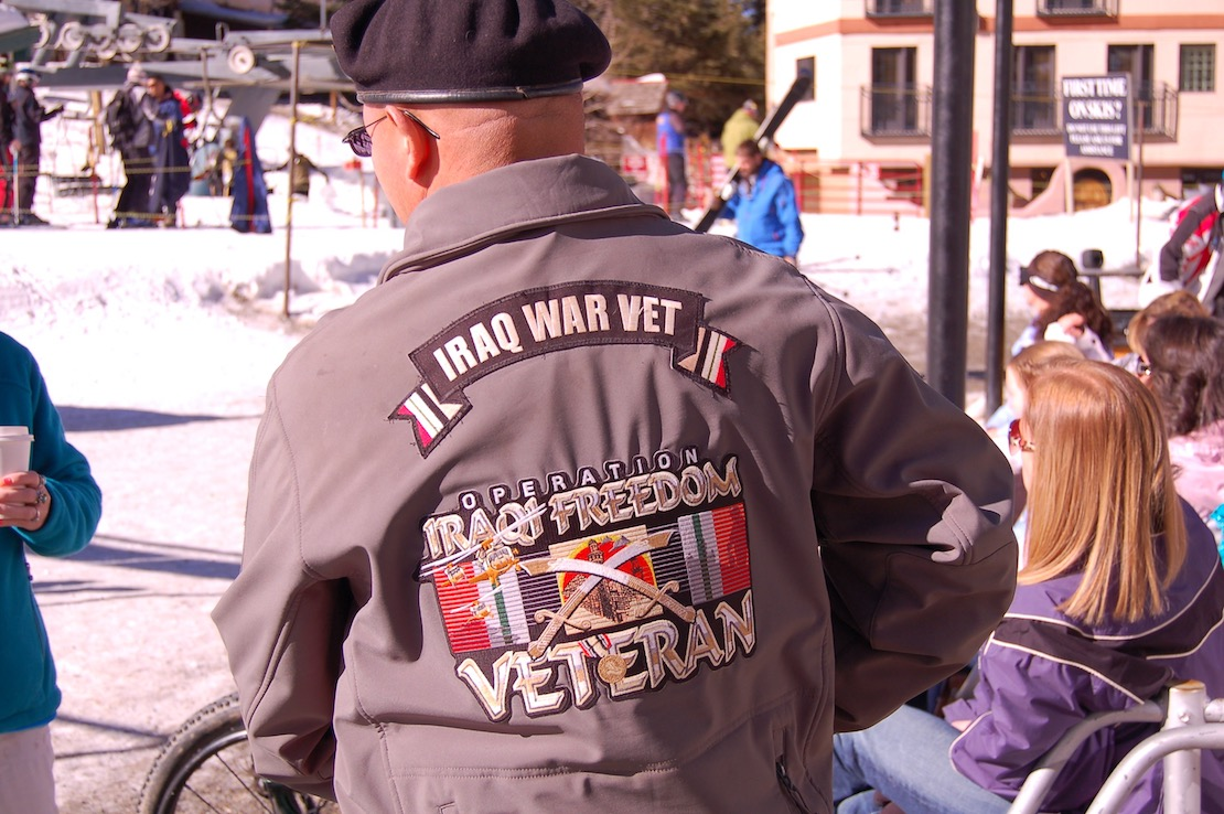 """Veteran facing away in black beret and gray jacket that says, """"Operation Iraqi Freedom,"""" standing outside at Taos Ski Valley"""